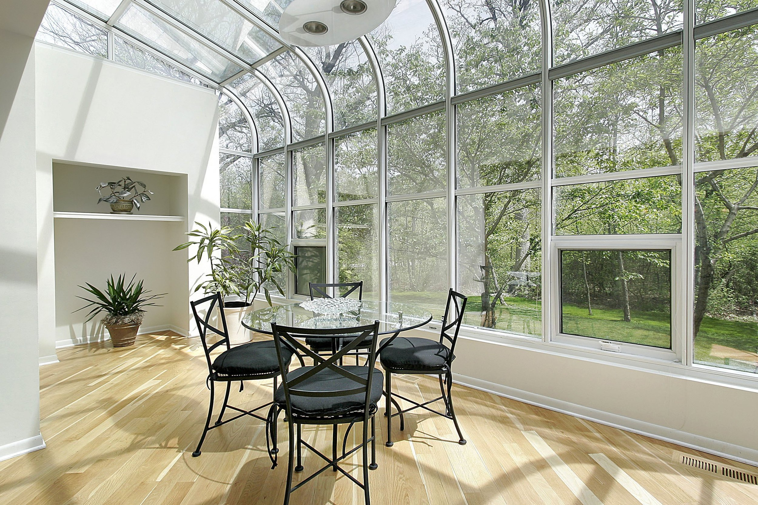 Small atrium style sunroom with wood floor and cafe table