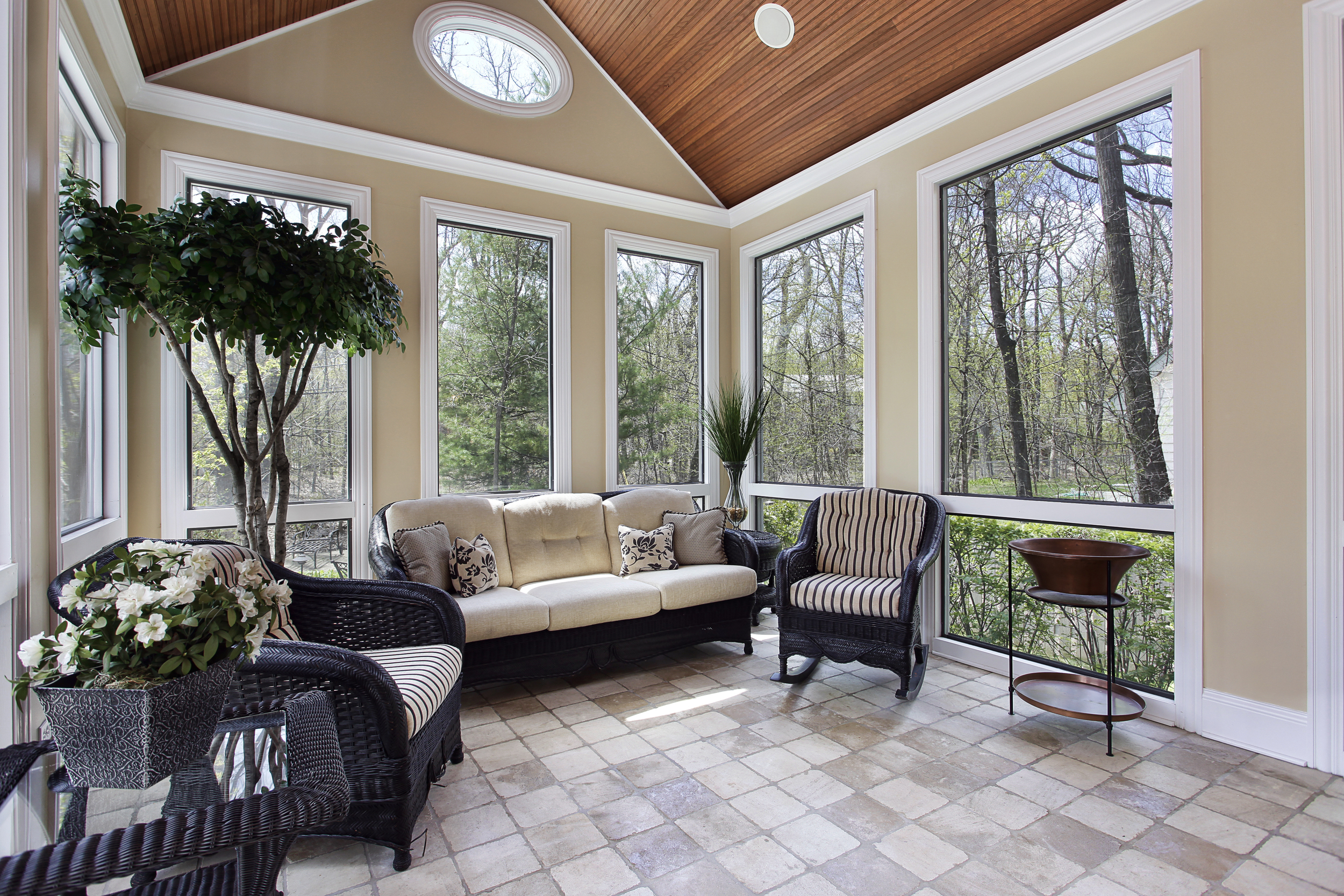 Small sunroom with tile, dark rattan couch and chairs, tan paint, wood ceiling.