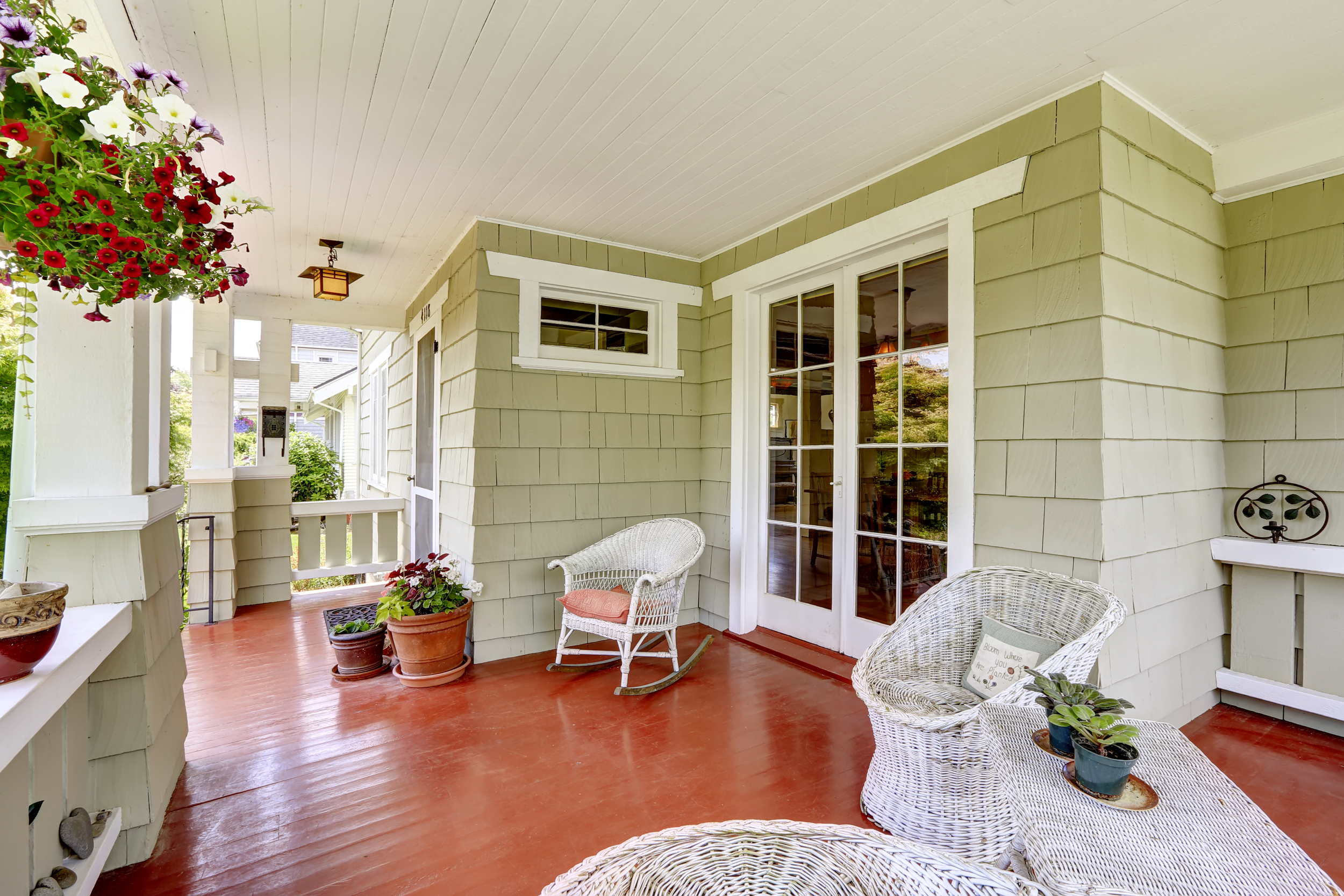 Front porch outdoor room with sitting area and sliding glass door, green paint, white furniture