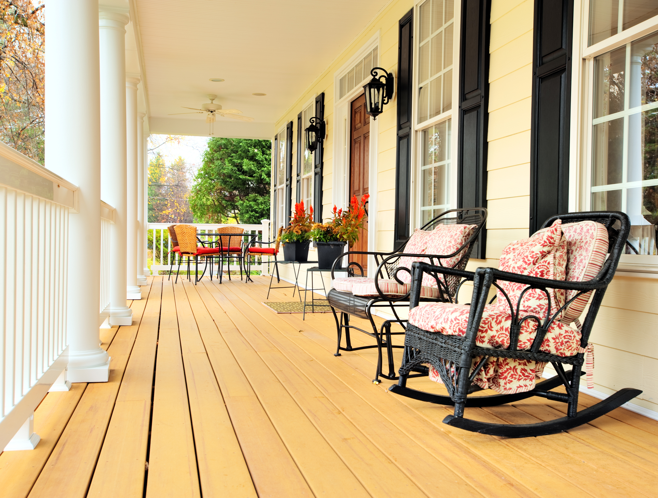 Long front porch with light wood, white paint, black furniture, red flowers