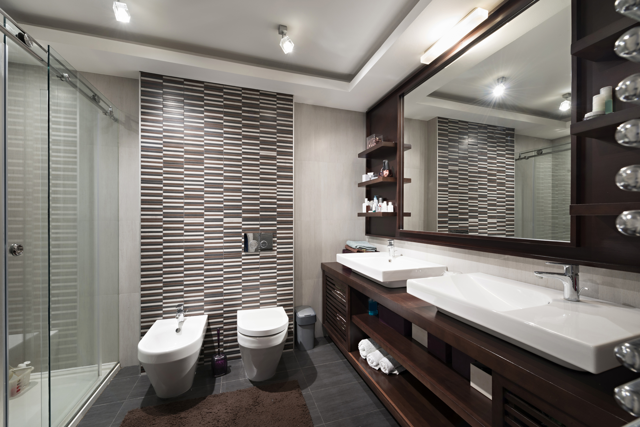 Medium bathroom with slate and brown tile, chocolate wood, white porcelain, walk-in shower, and bidet