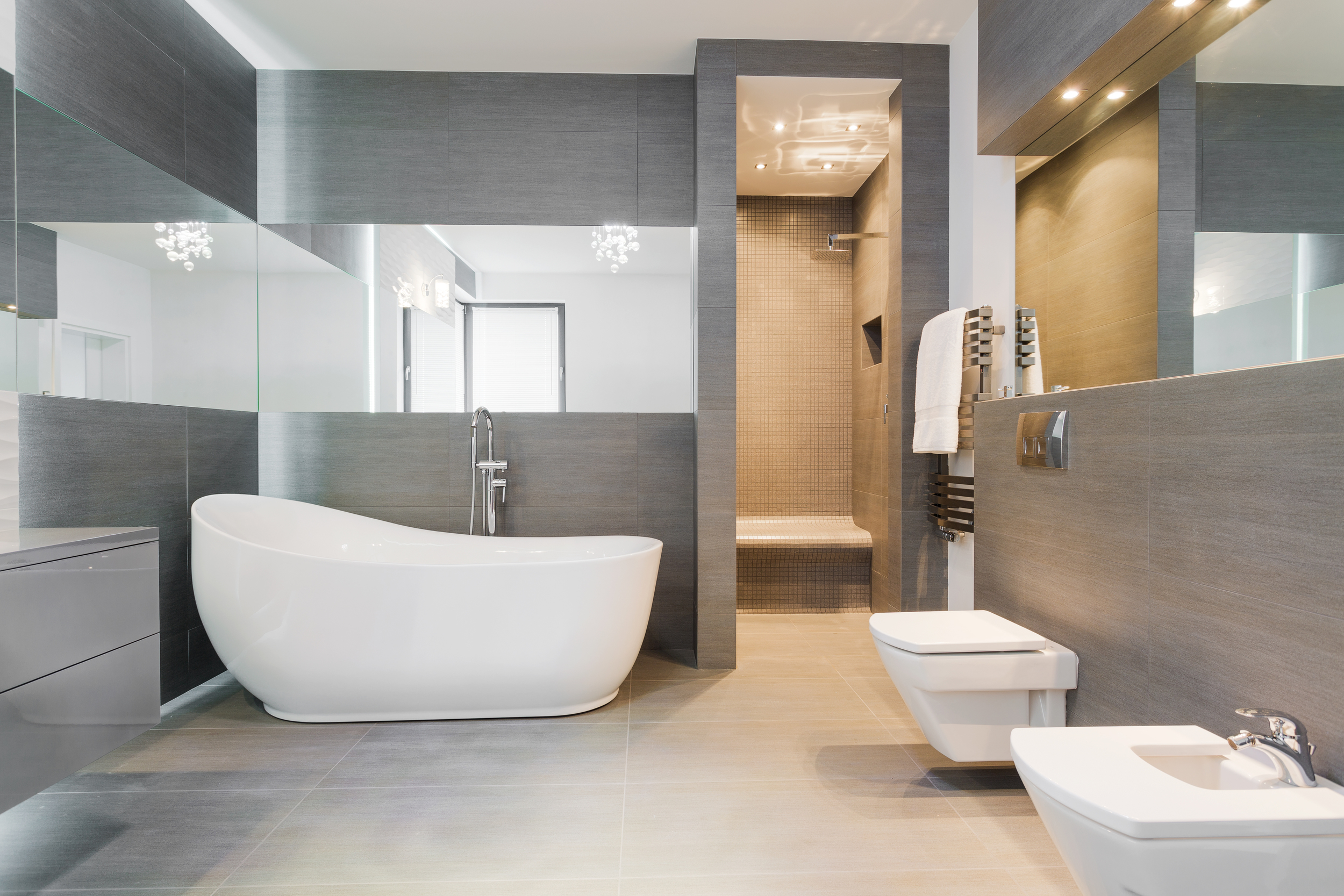 Large modern bathroom with grey tile, tub, walk-in shower, and wrap around mirrors