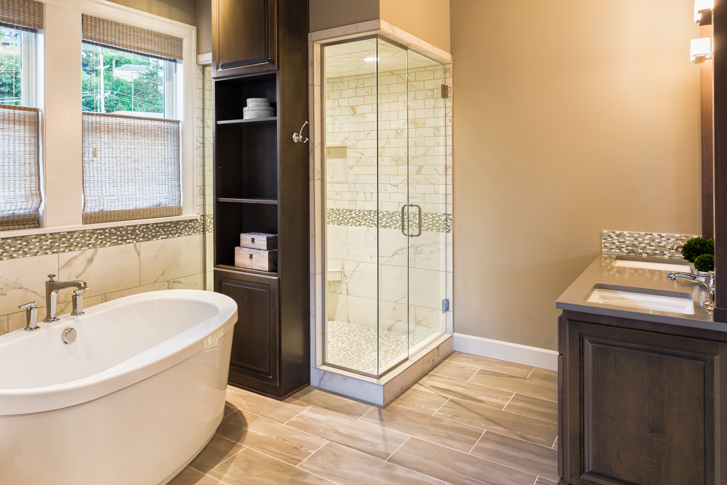Medium bathroom with tan tile and paint, bath, walk-in shower, built-in linen storage, and double sinks
