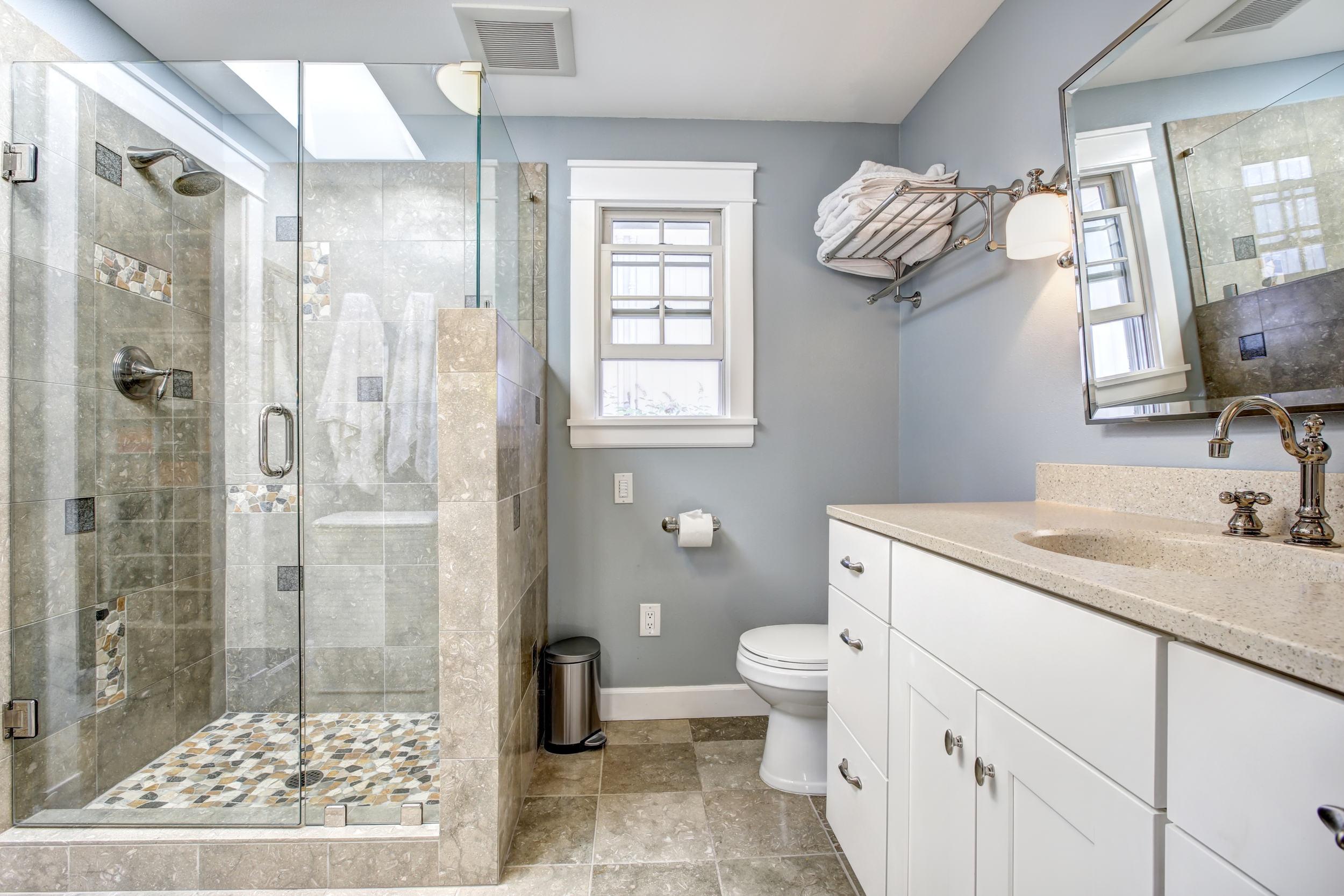 Small bathroom with blue-grey paint, tan tile, white trim, and walk-in shower