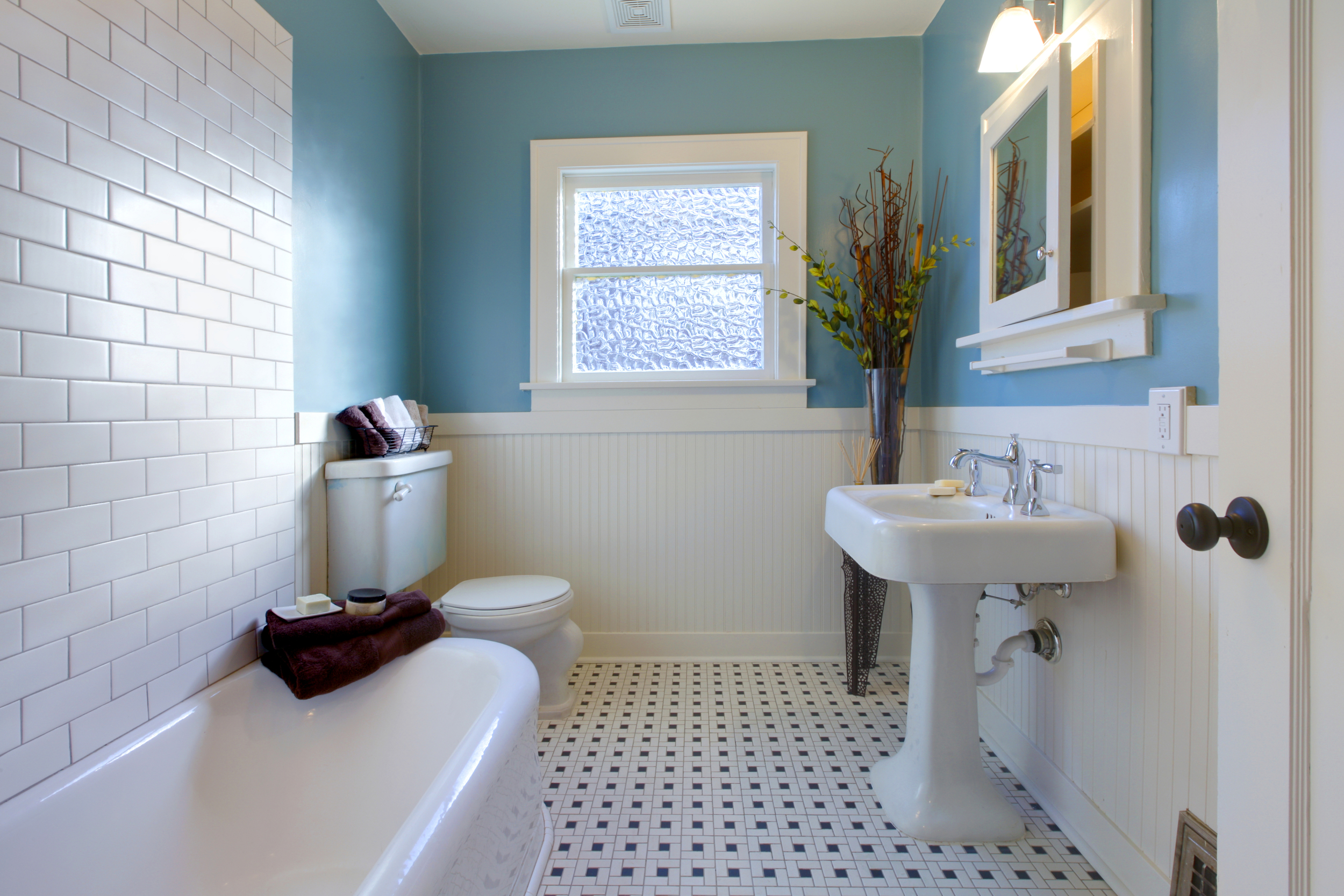 Small retro bathroom with black and white tile, teal paint, bath, and pedistol sink