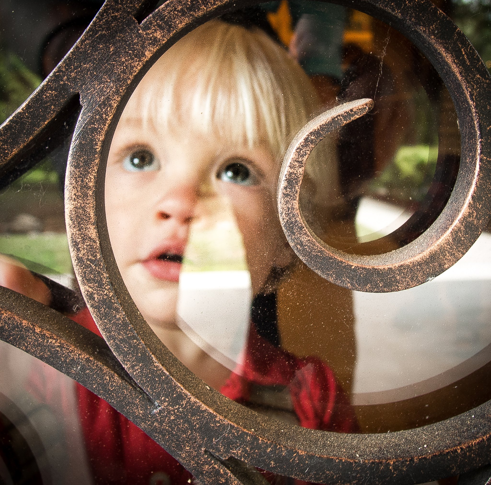 young child peering up through window
