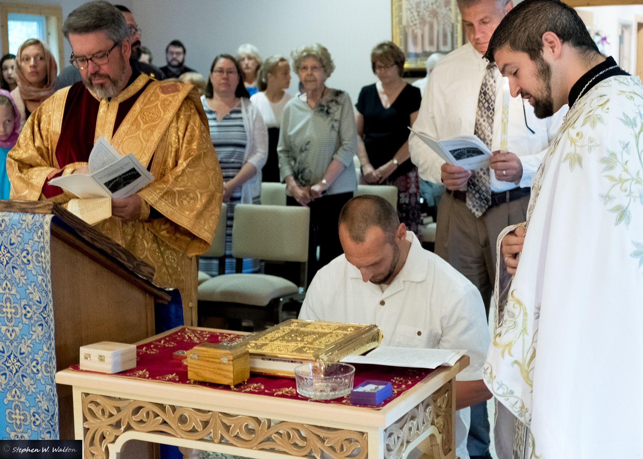 Theophan kneels before the Gospel and Cross, professing the faith of the Ancient Orthodox Christian Church