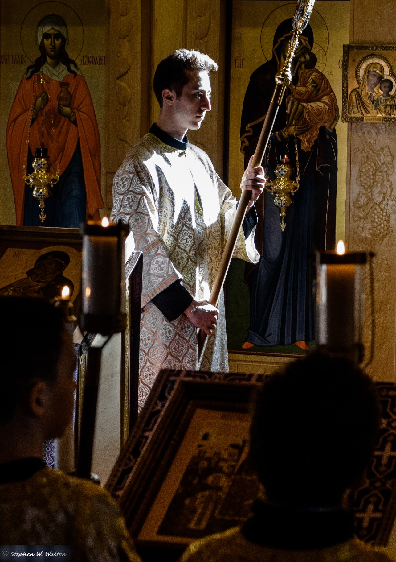 altar server holding processional fan in low light