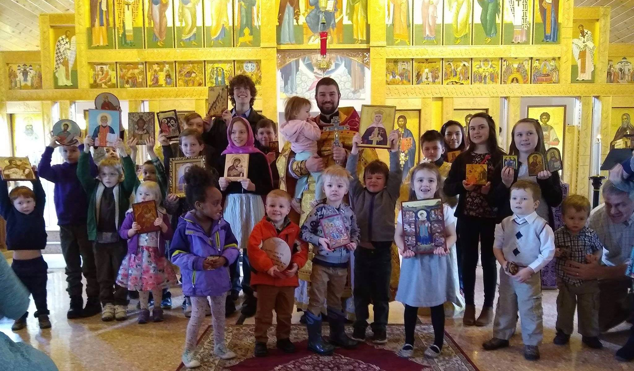 group picture of children holding icons with priest