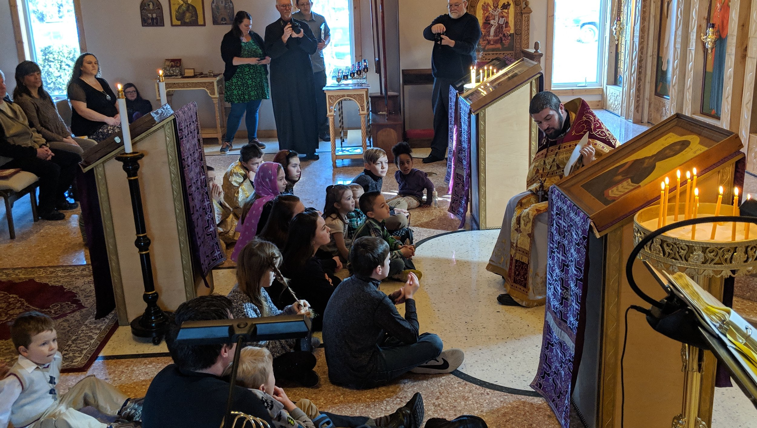 children sitting in front of priest while he reads to them with parents sitting in background