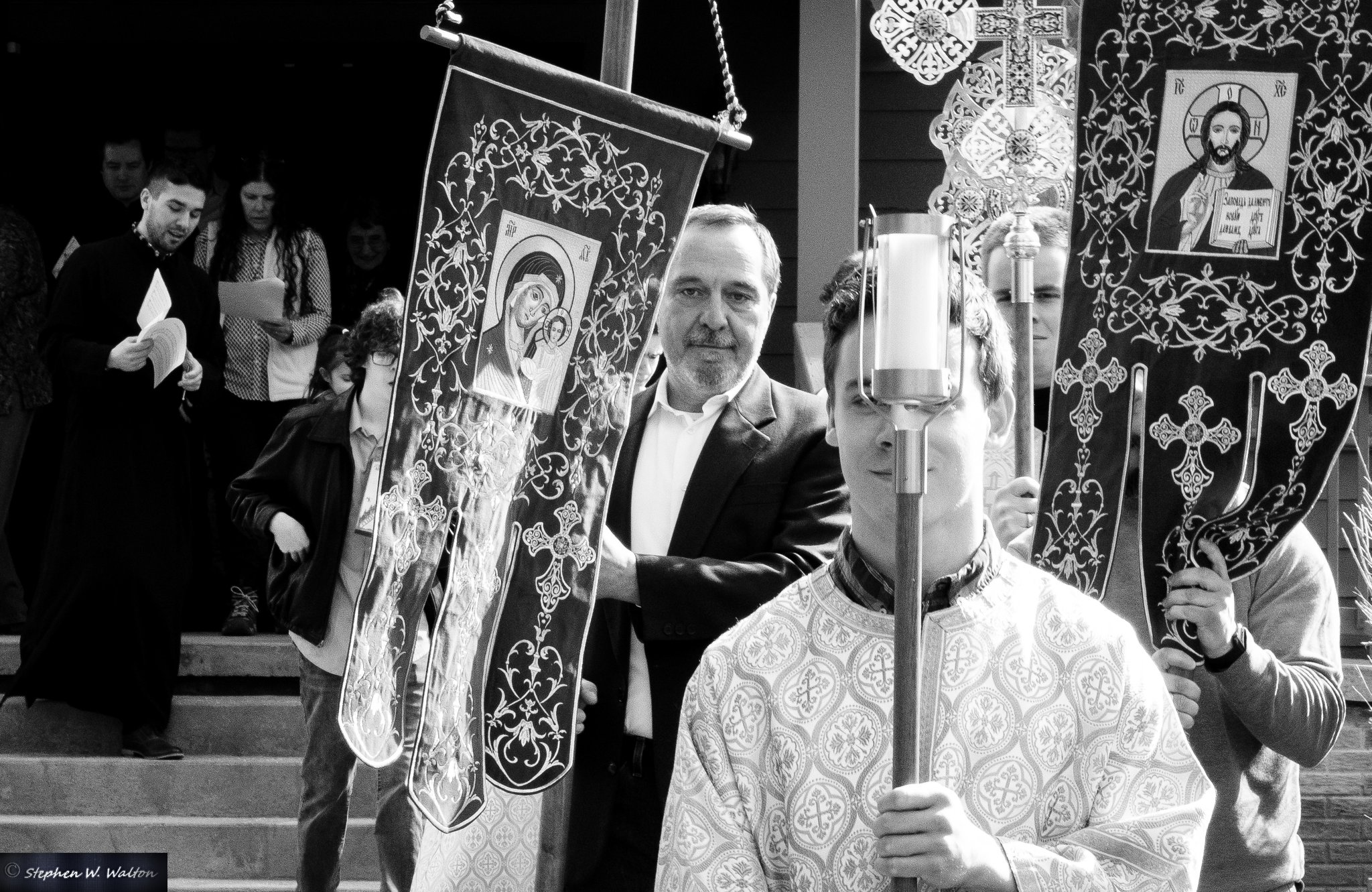altar server holding candle with parishioners carrying icon banners in procession outside black and white