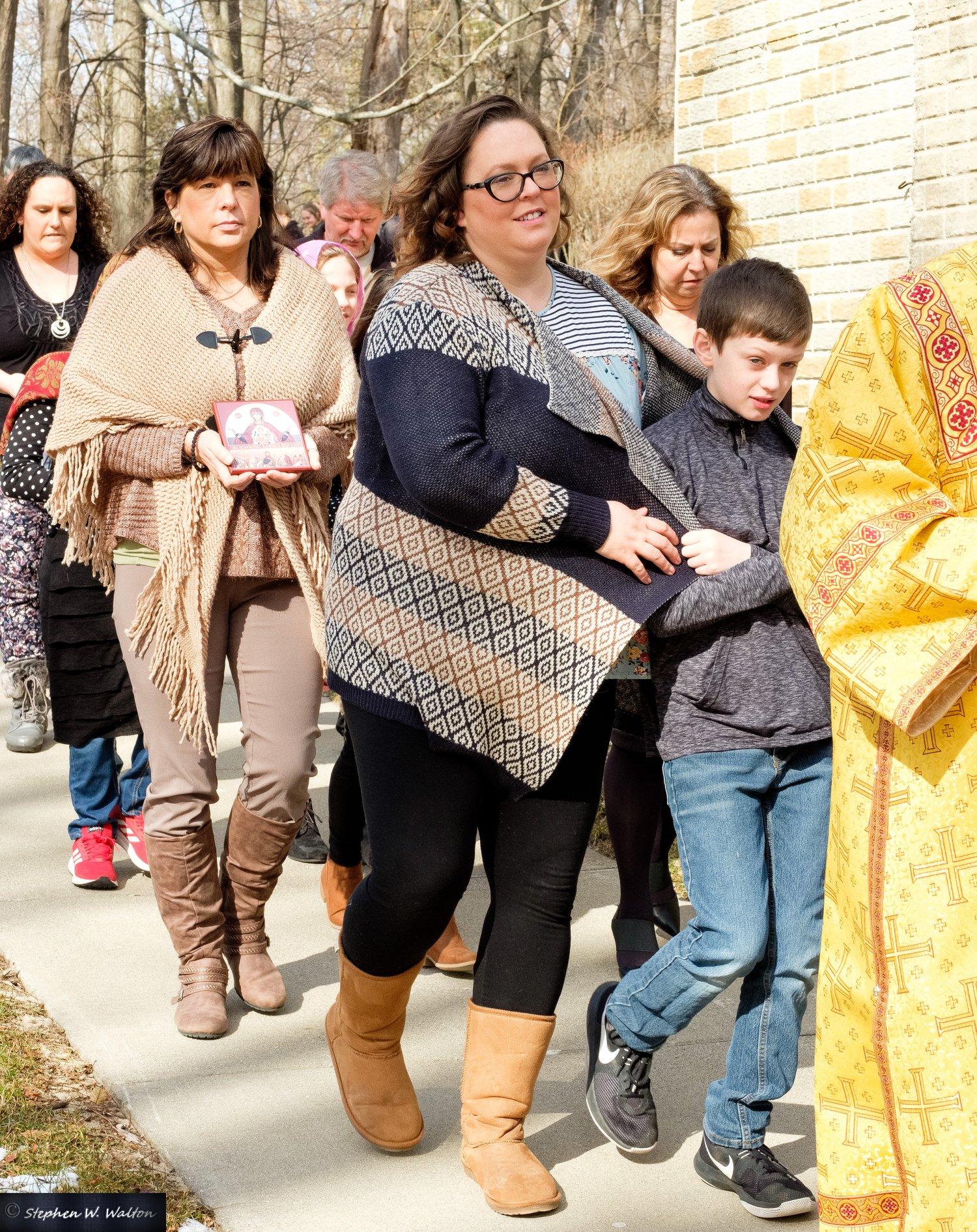 parishioners in procession outside holding icons