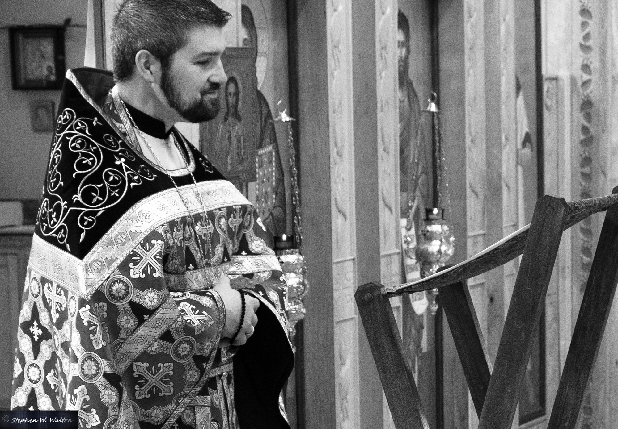 priest giving sermon looking at notes on lectern black and white