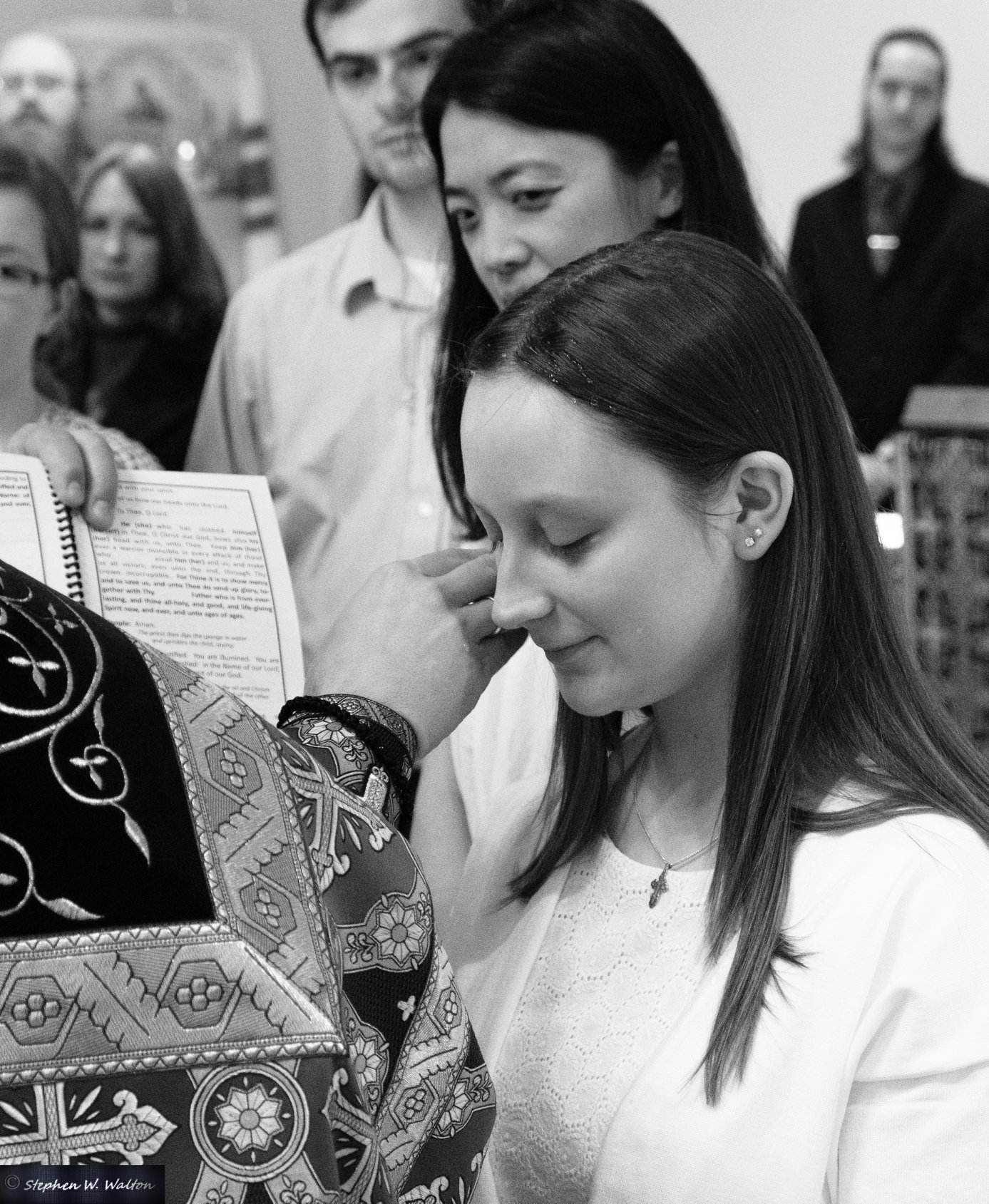 priest anointing young woman for chrismation black and white