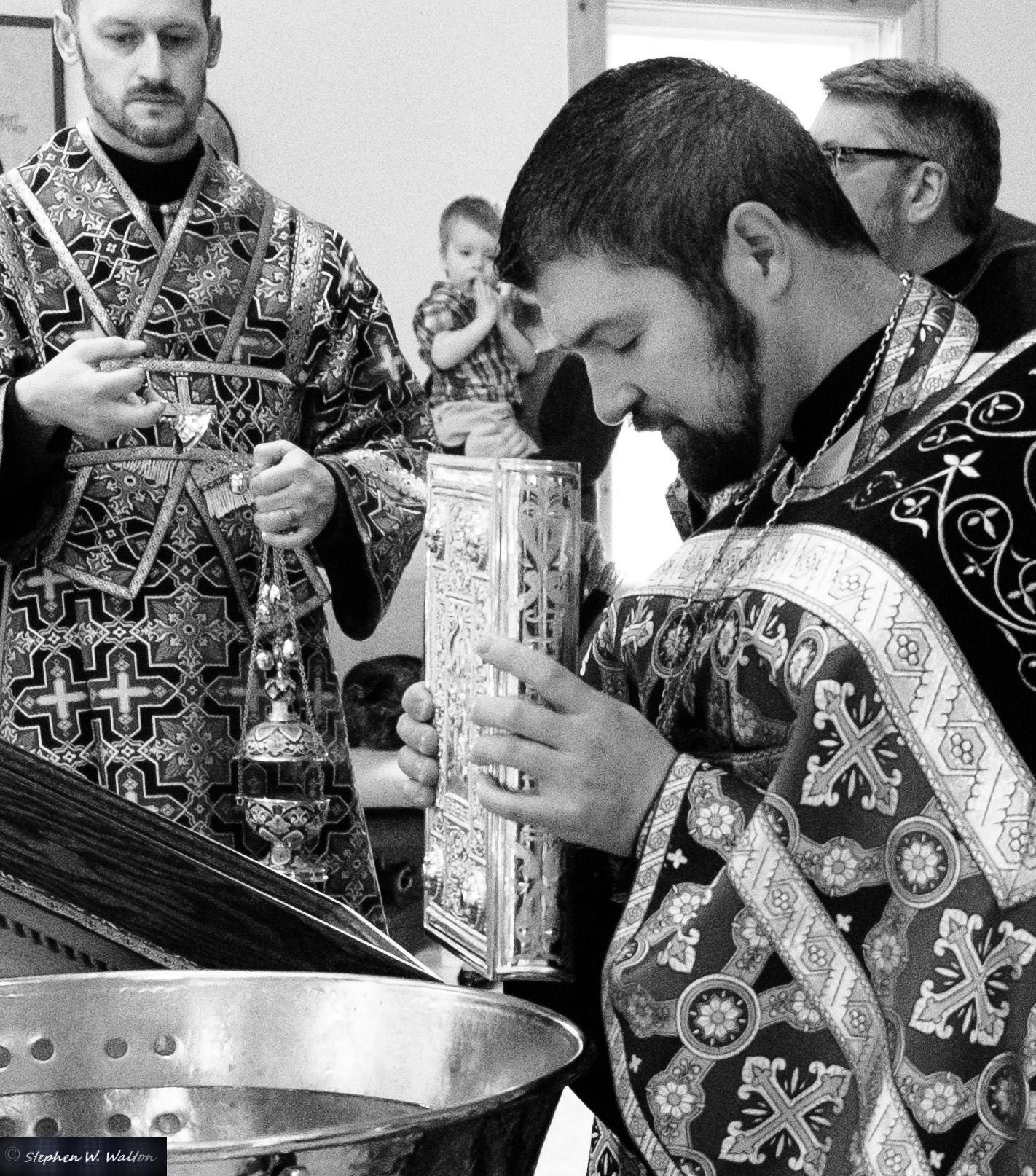 priest blessing baptismal font with gospel