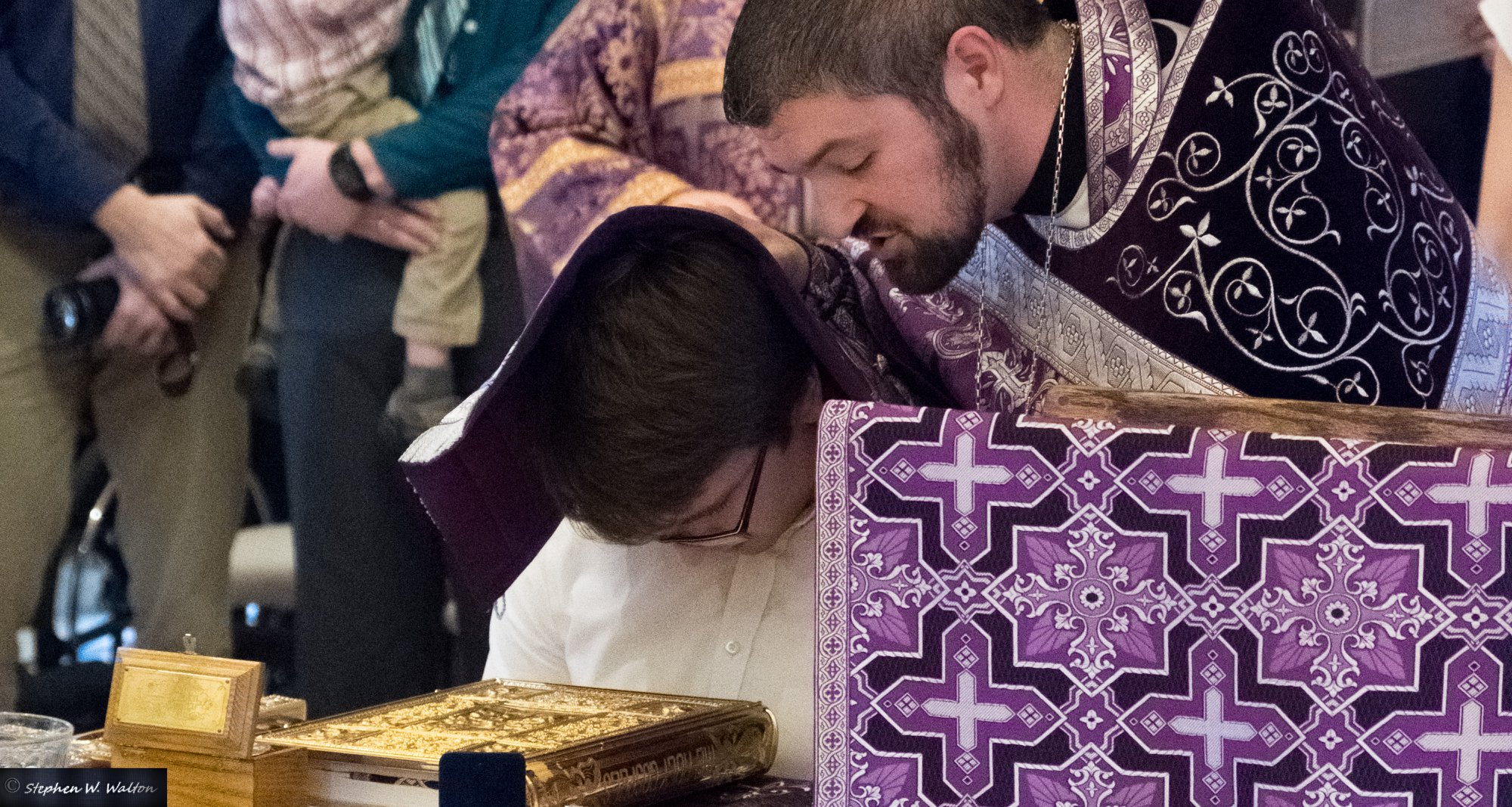 priest covering head of young male with stole offering prayers of absolution