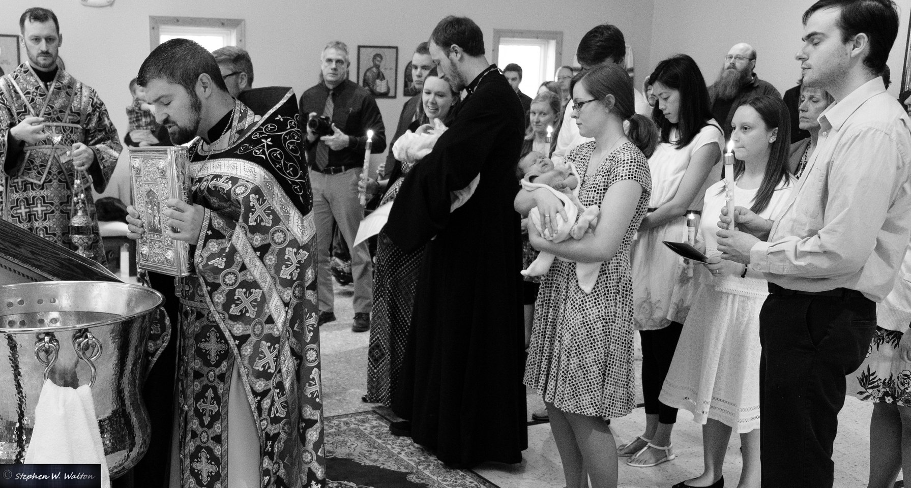 priest leading newly received in procession around the baptismal font black and white