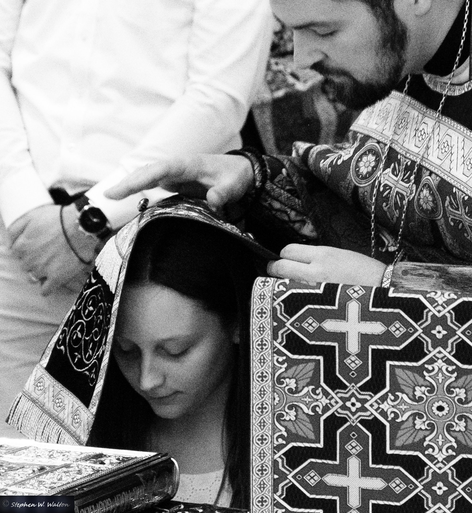 priest with stole covering head of young woman offering prayers of absolution