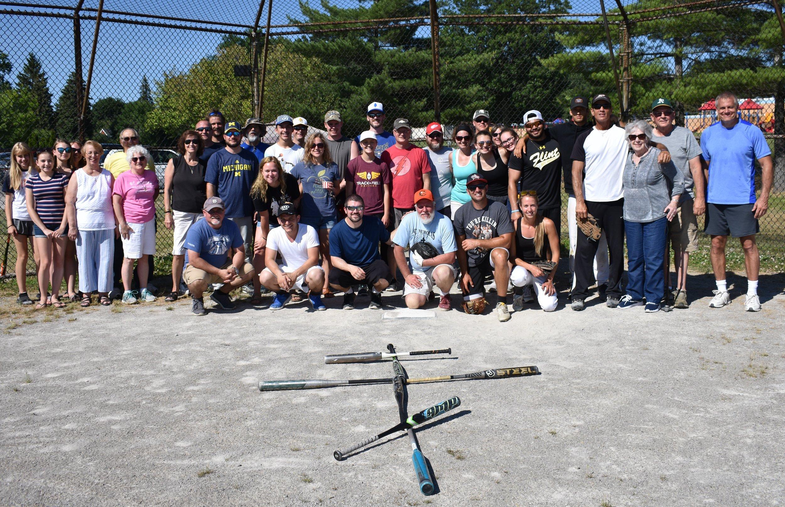 Participants of pan orthodox softball game behind home plate with bats in shape of cross in foreground