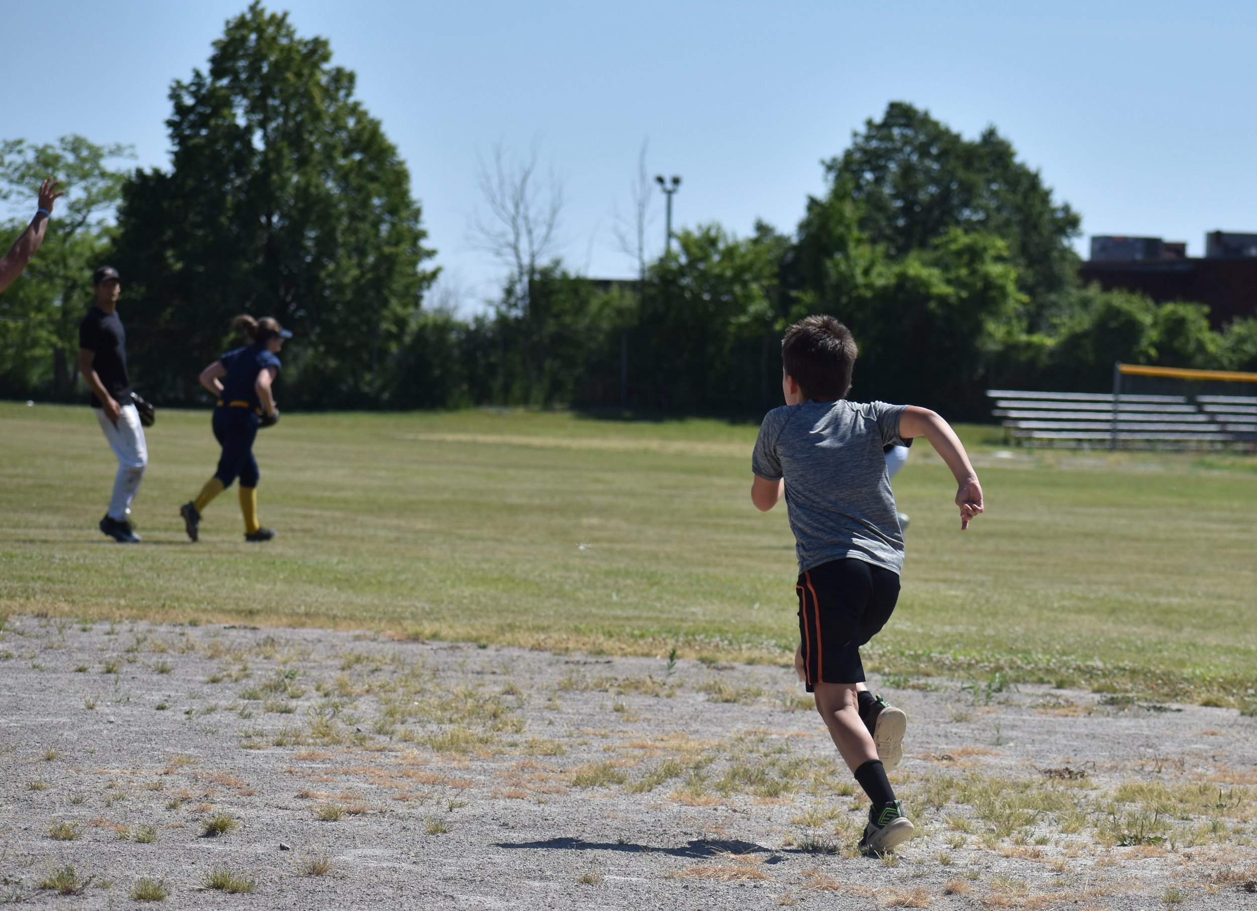 young boy running to second base