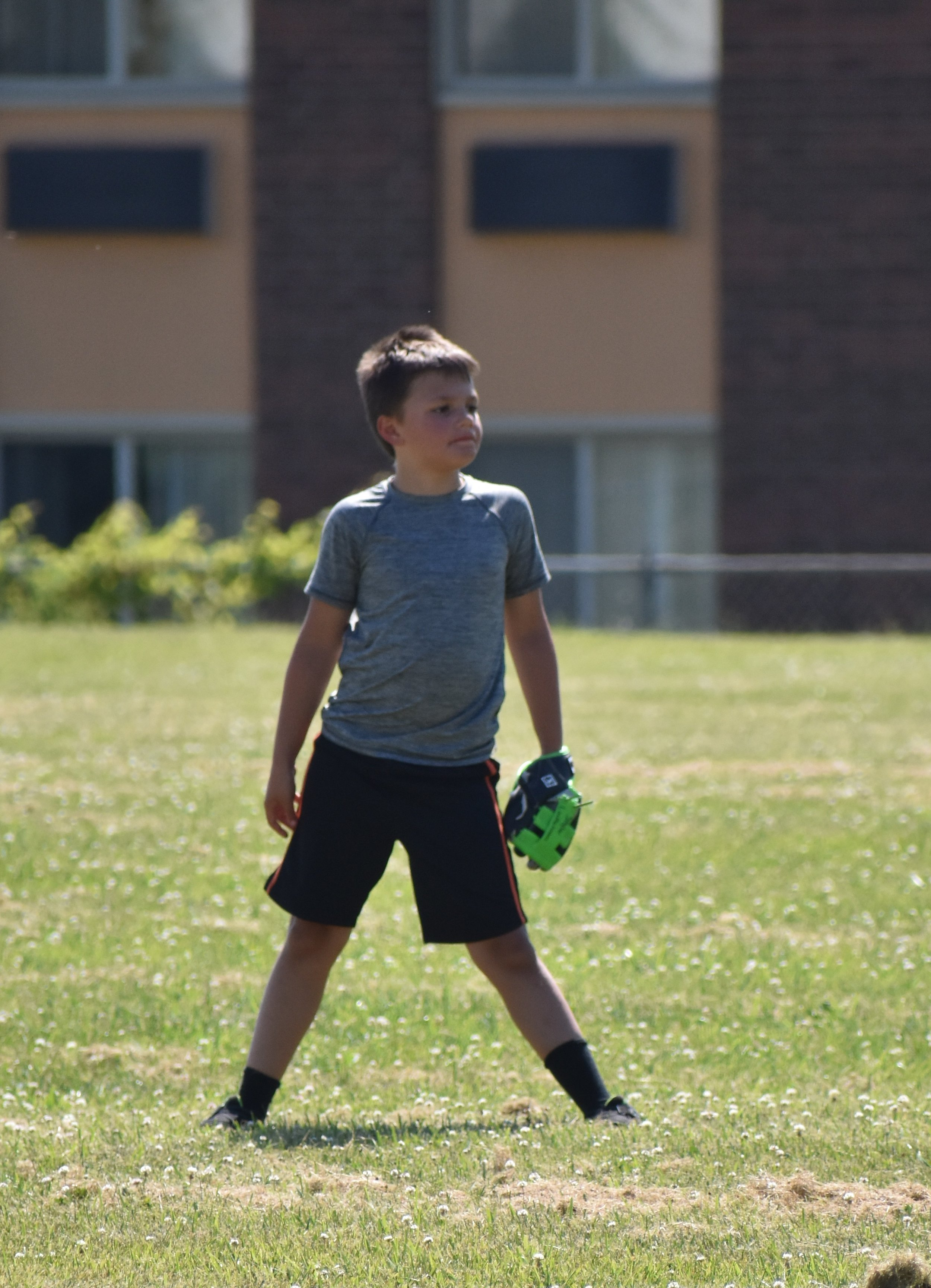 young boy standing in outfield