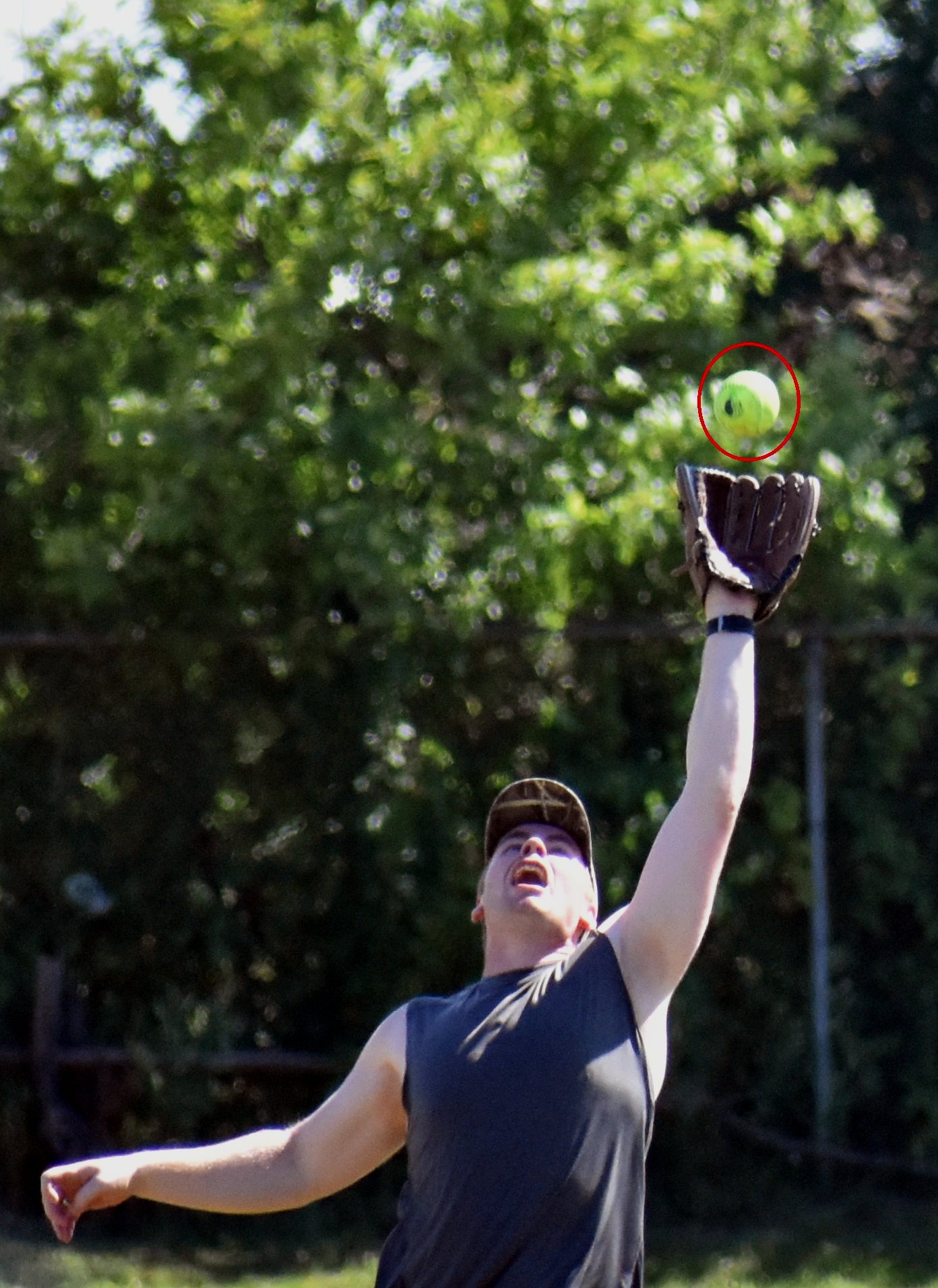male player reaching to catch fly ball