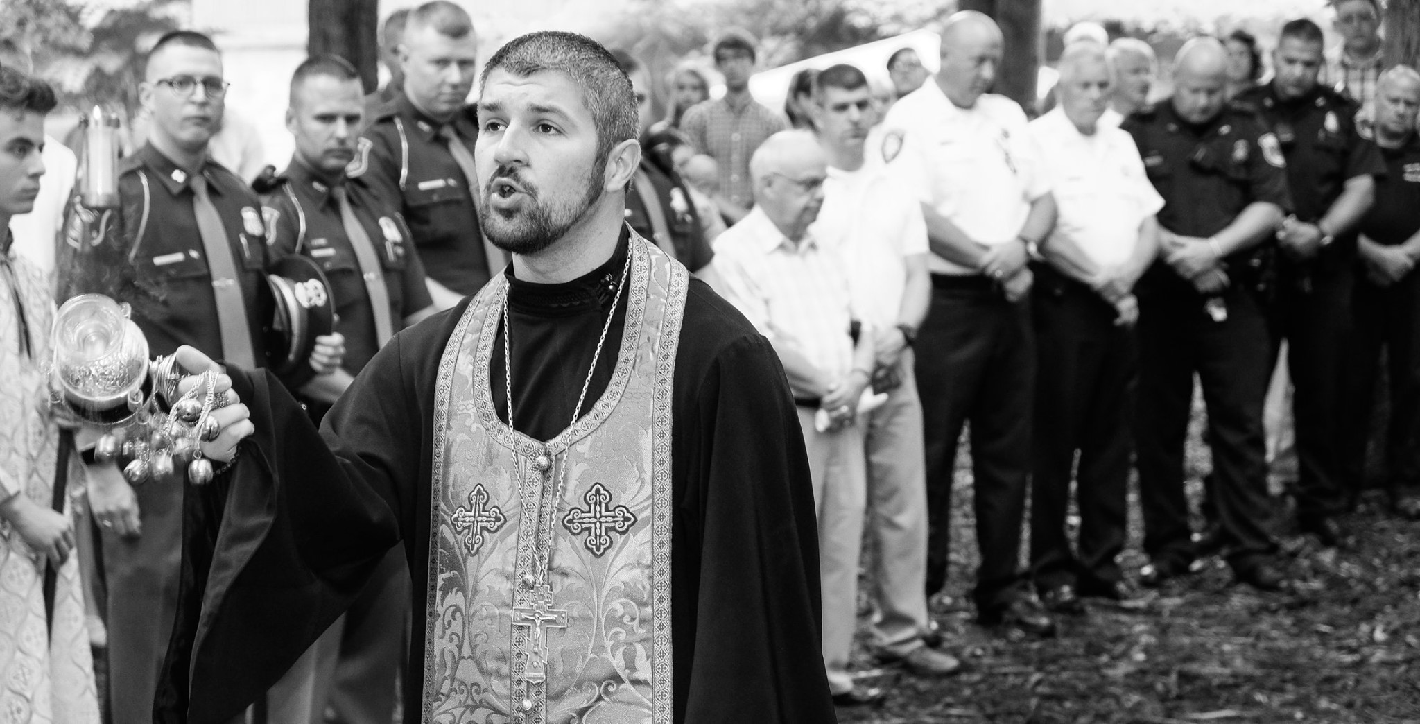 priest censing and praying with first responders in background black and white