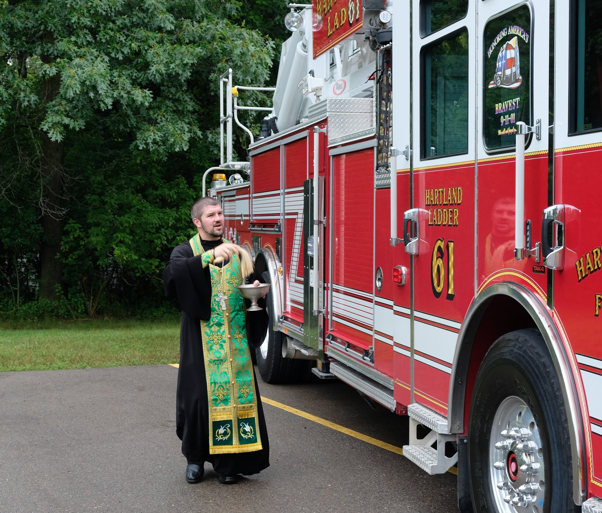 priest blessing fire truck with holy water
