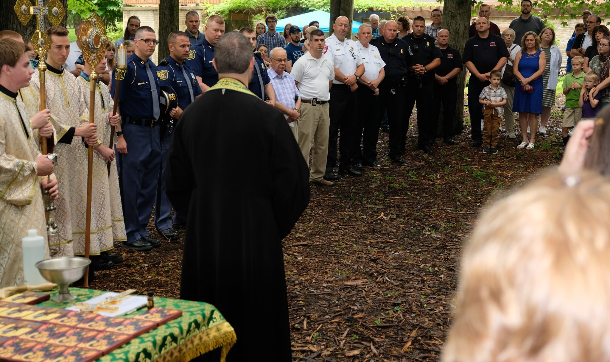 priest facing crowd of parishioners and first responders