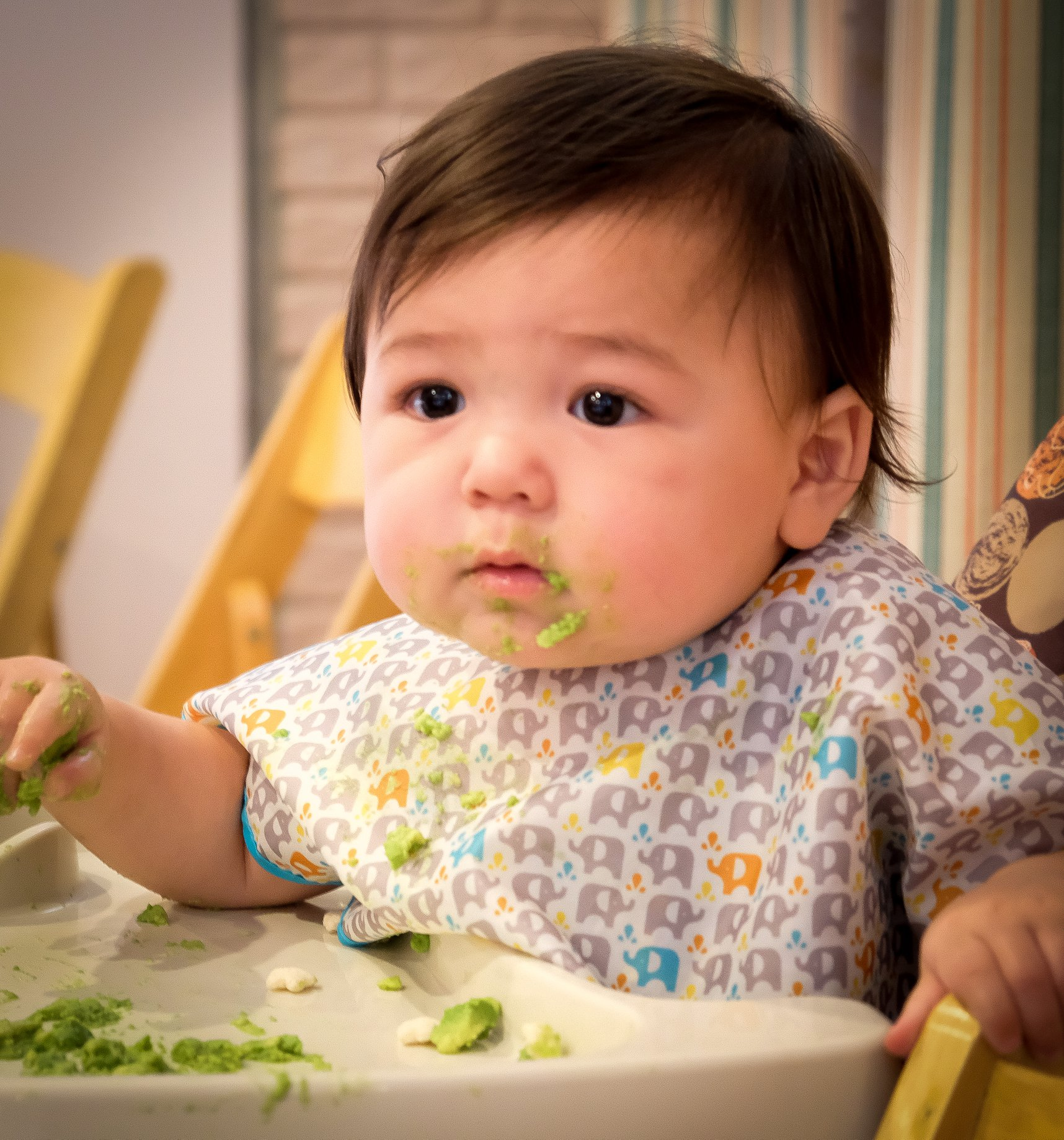 baby girl  in high chair eating with green peas on chin