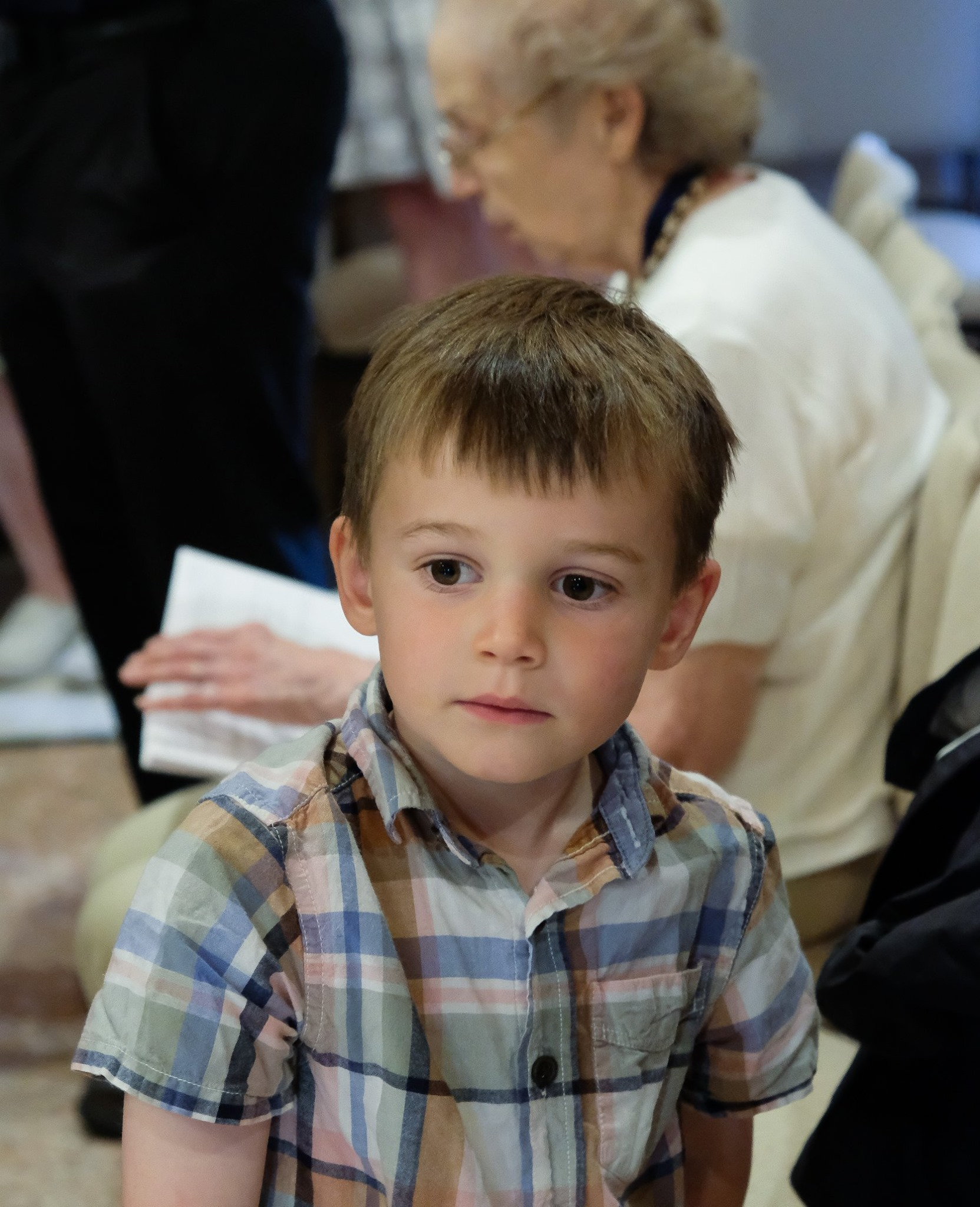 small boy in plaid shirt during service