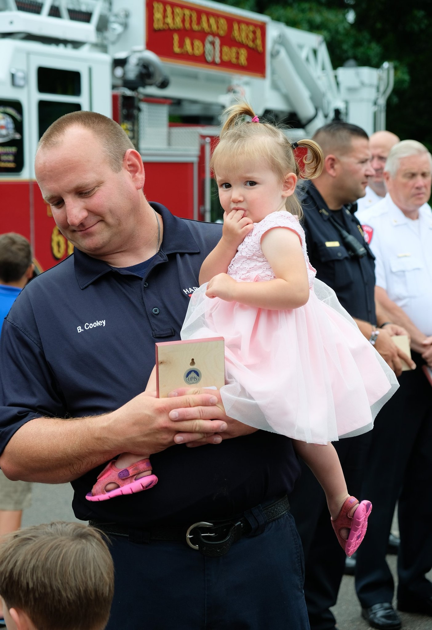 first responder father holding toddler daughter in pink dress