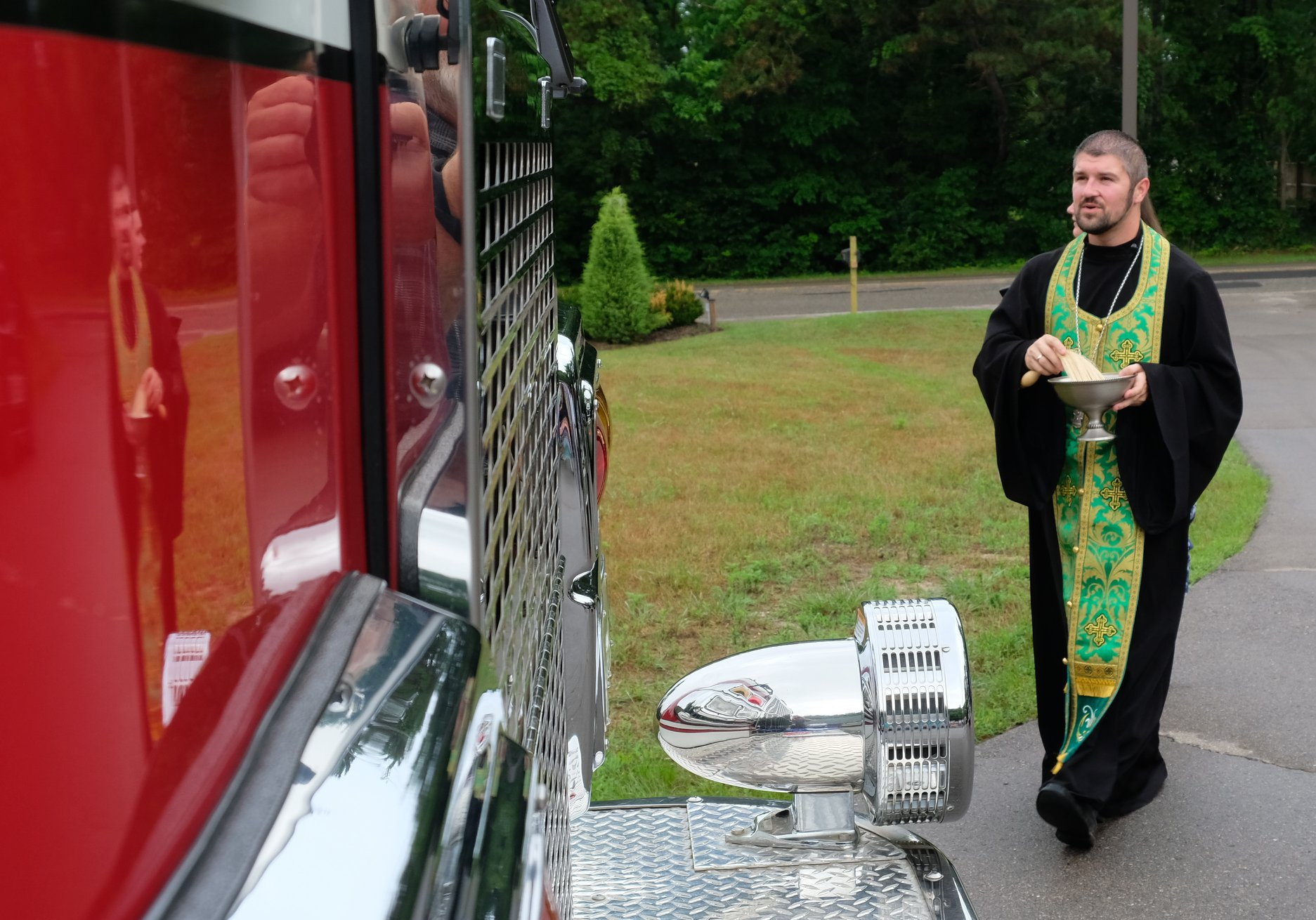 priest walking to fire truck to bless with holy water
