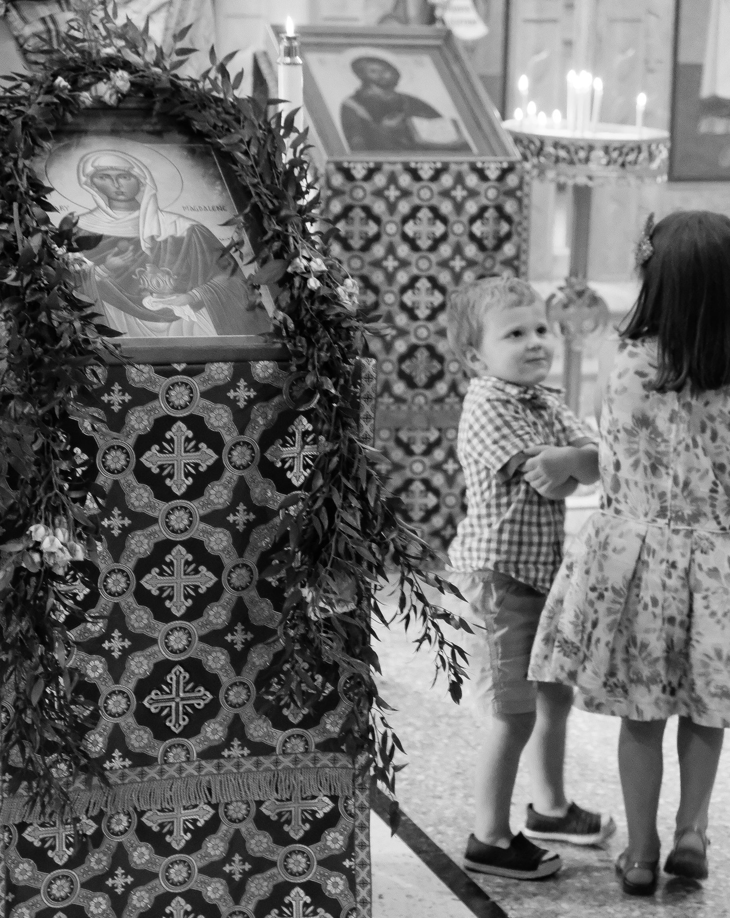 young boy and girl standing next to icon stands black and white