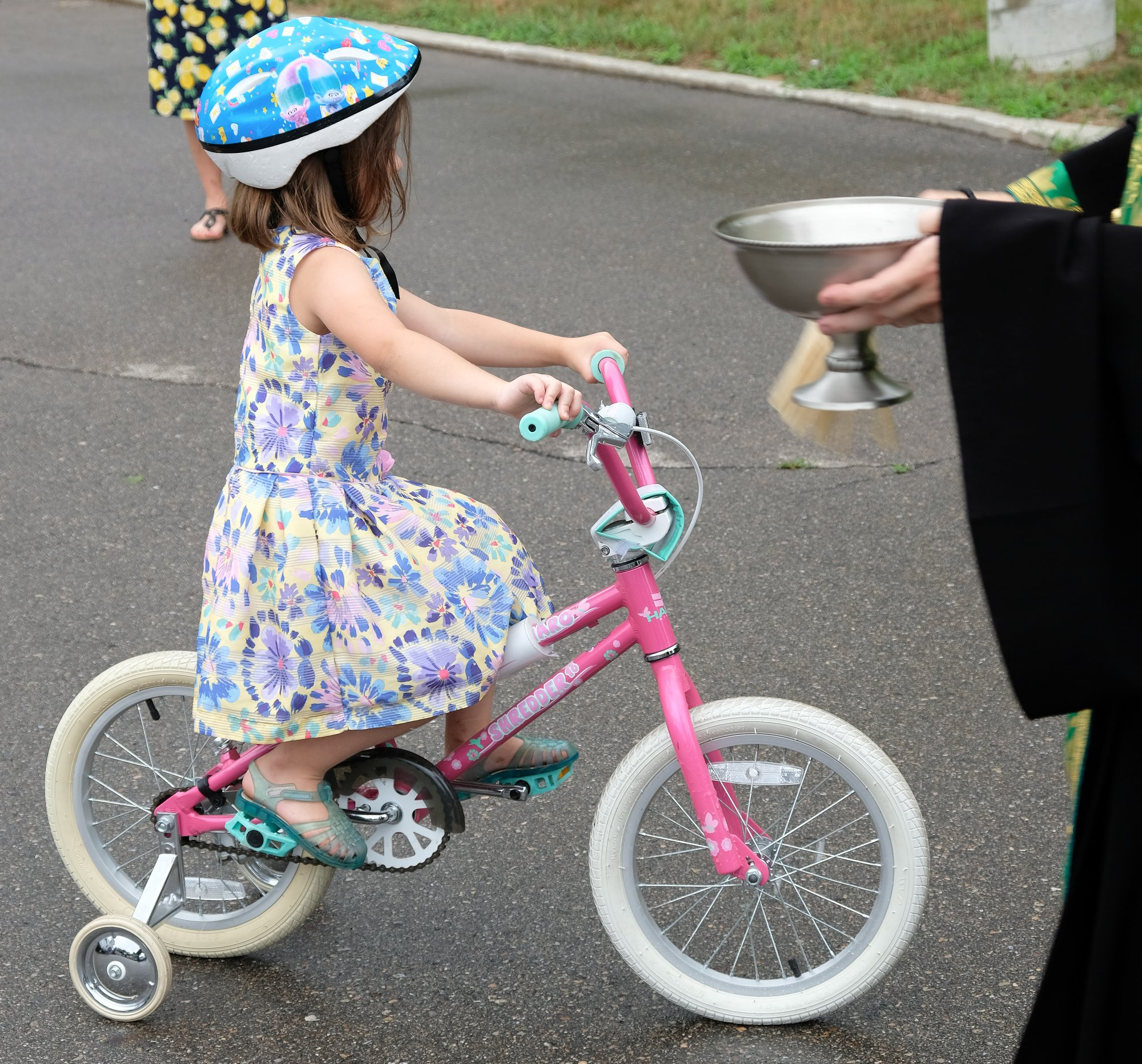 priest blessing young girl on a pink bike