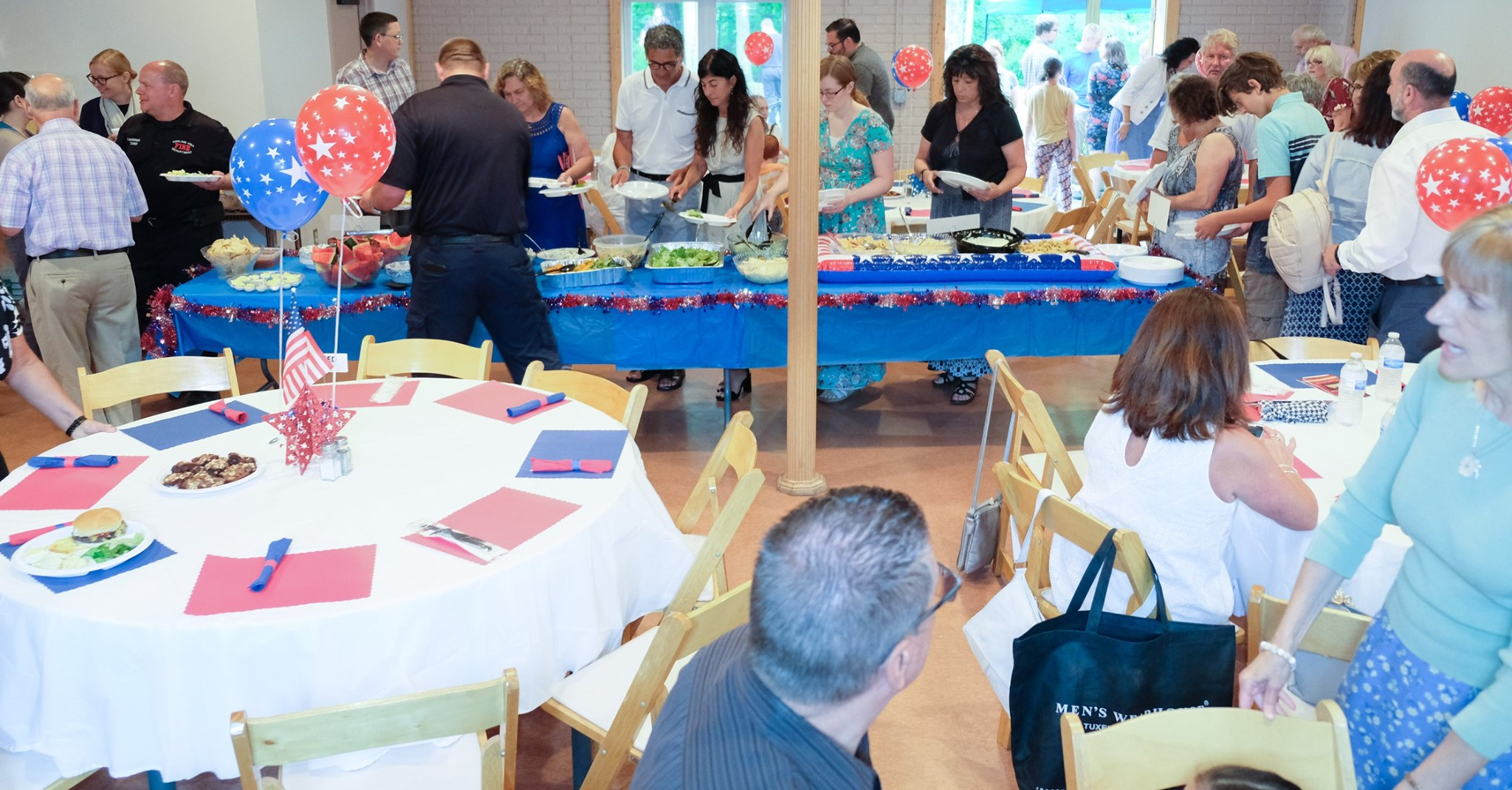 people in line for food with tables set in forefront