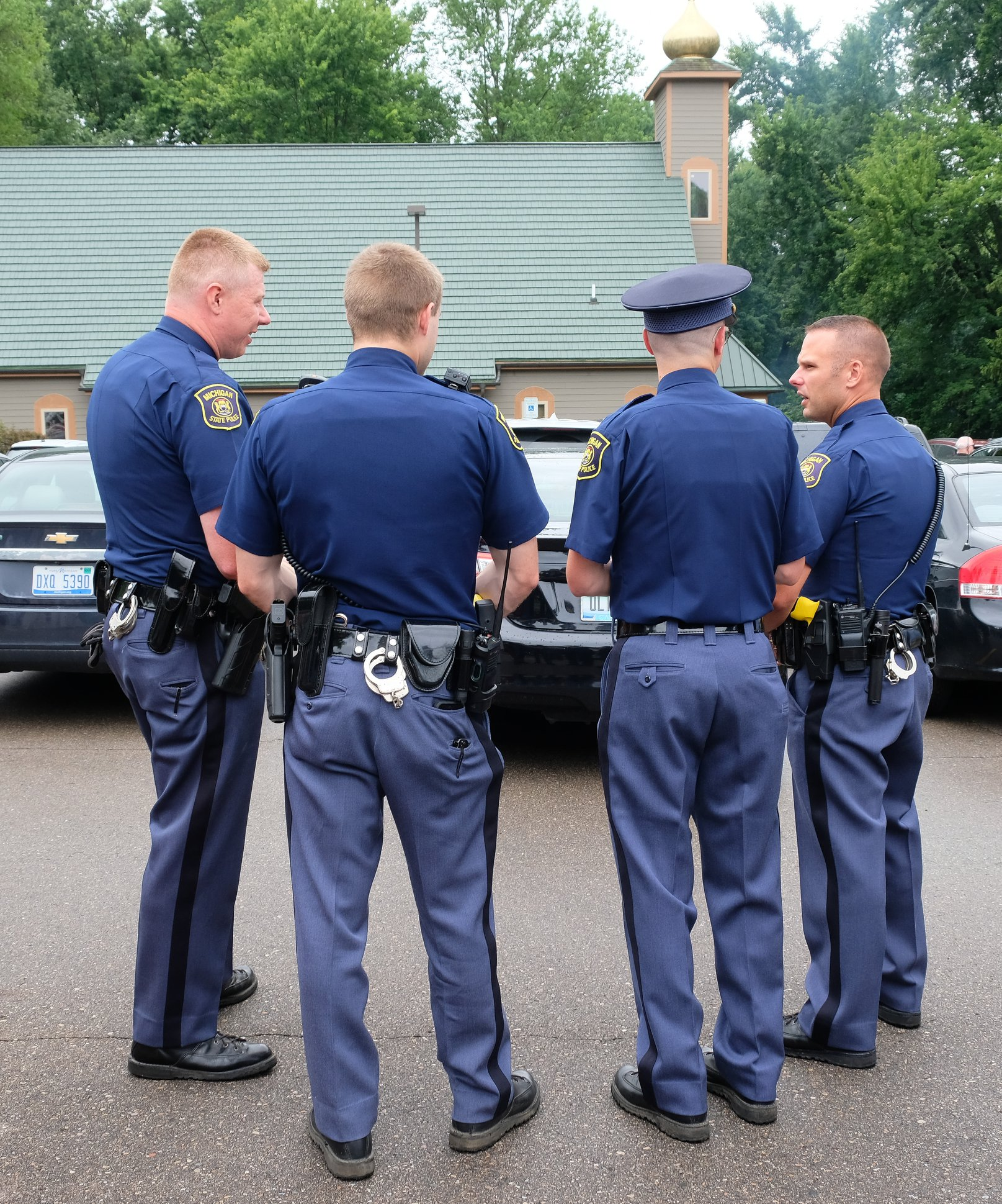 four state troopers standing together in church parking lot