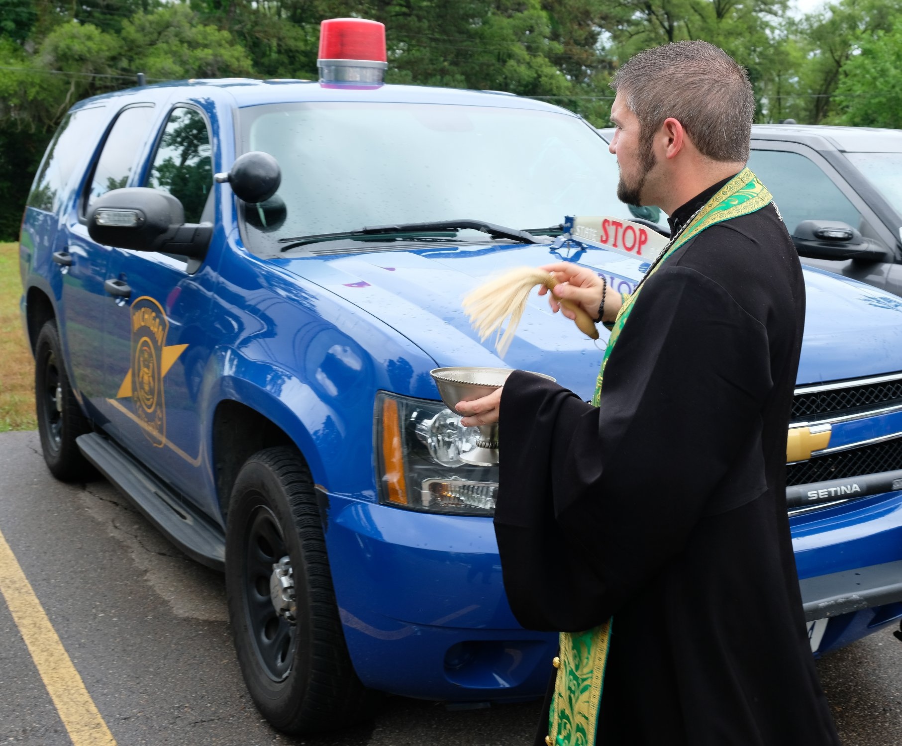 priest blessing state trooper SUV with holy water