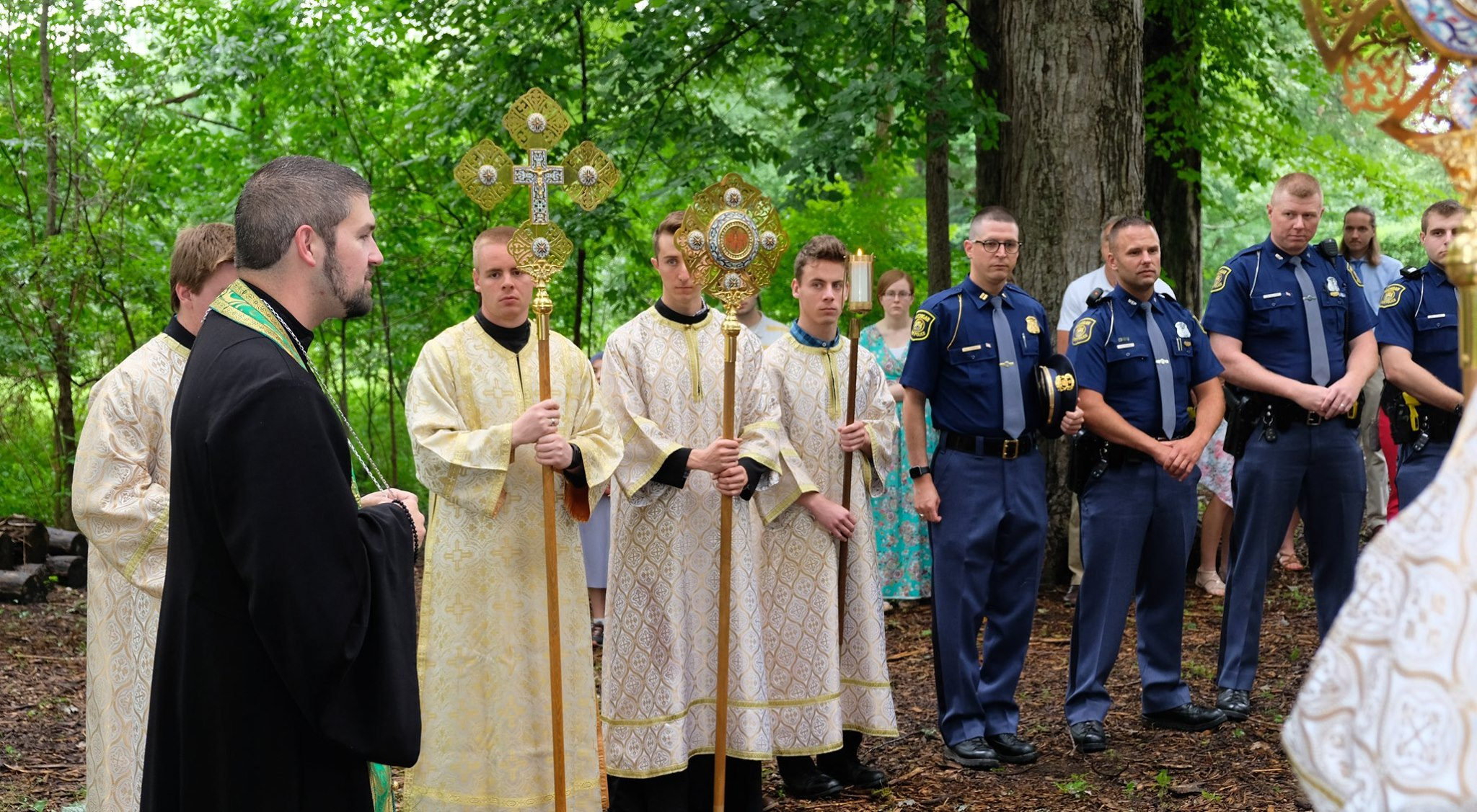altar servers lined up next to state troopers with priest speaking