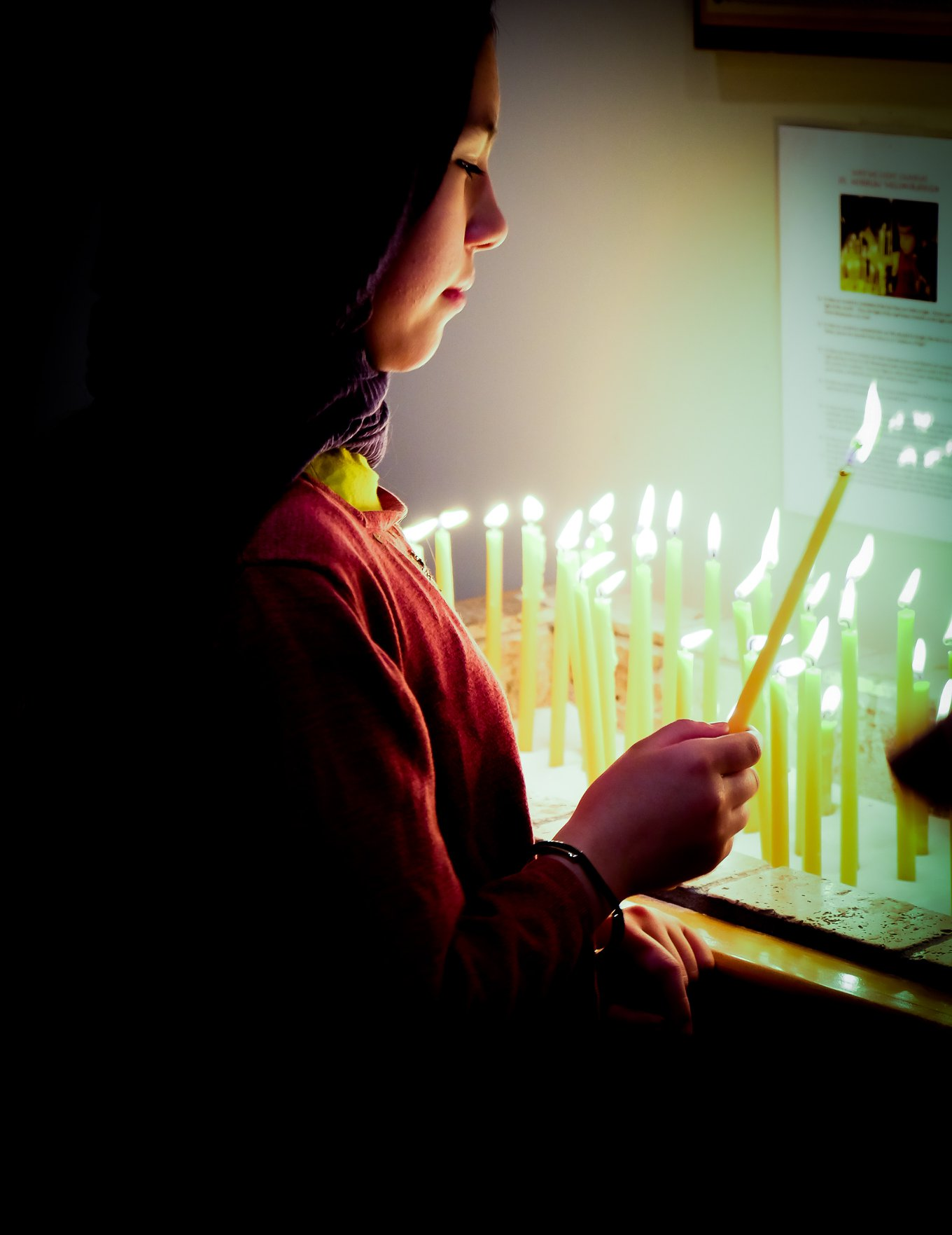 young girl lighting candle from candle stand in shadow