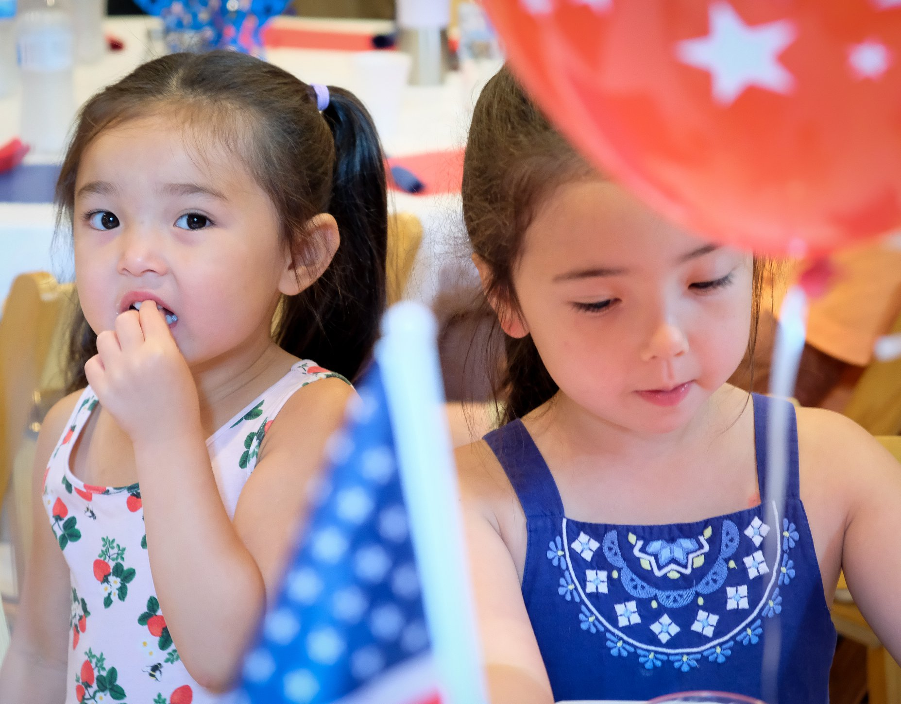 two sisters eating with balloon in forefront