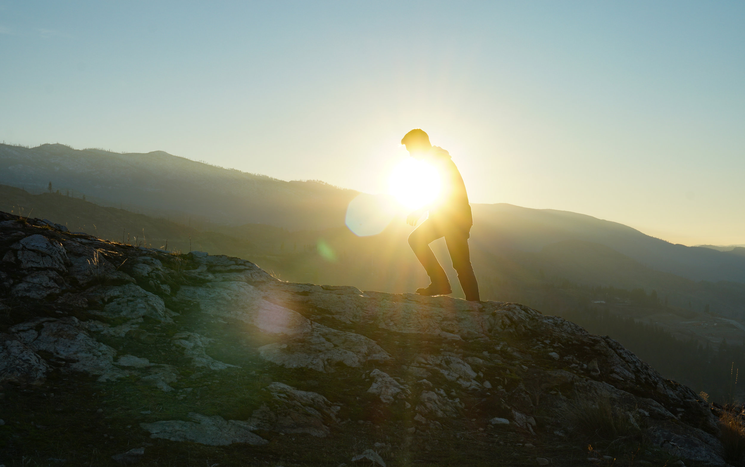 man walking uphill with sun shining behind him showing only the mans silhouette