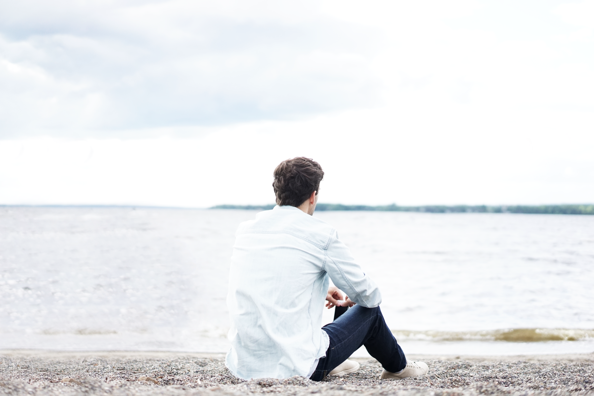man sitting on beach looking out into the water