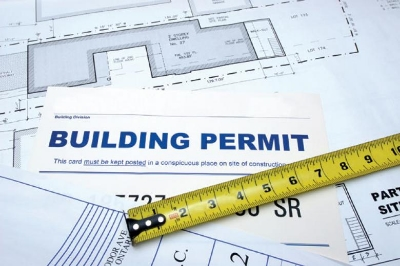 Illustration showing building permit, architectural plans and a tape measure