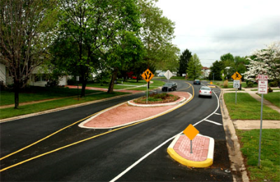 Suburban traffic calming lanes with streetscaped island.