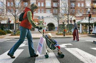Woman in crosswalk with small child in stroller.