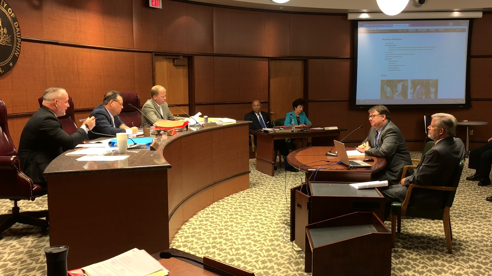 At a July 12 public hearing of the Dauphin County Commissioners, TCRPC staffers Jerry Duke and Steve Deck, right, offer a presentation on the county's new 10-year  comprehensive plan . Commissioners George P. Hartwick III, Jeff Haste and Mike Pries, left, unanimously approved the plan.
