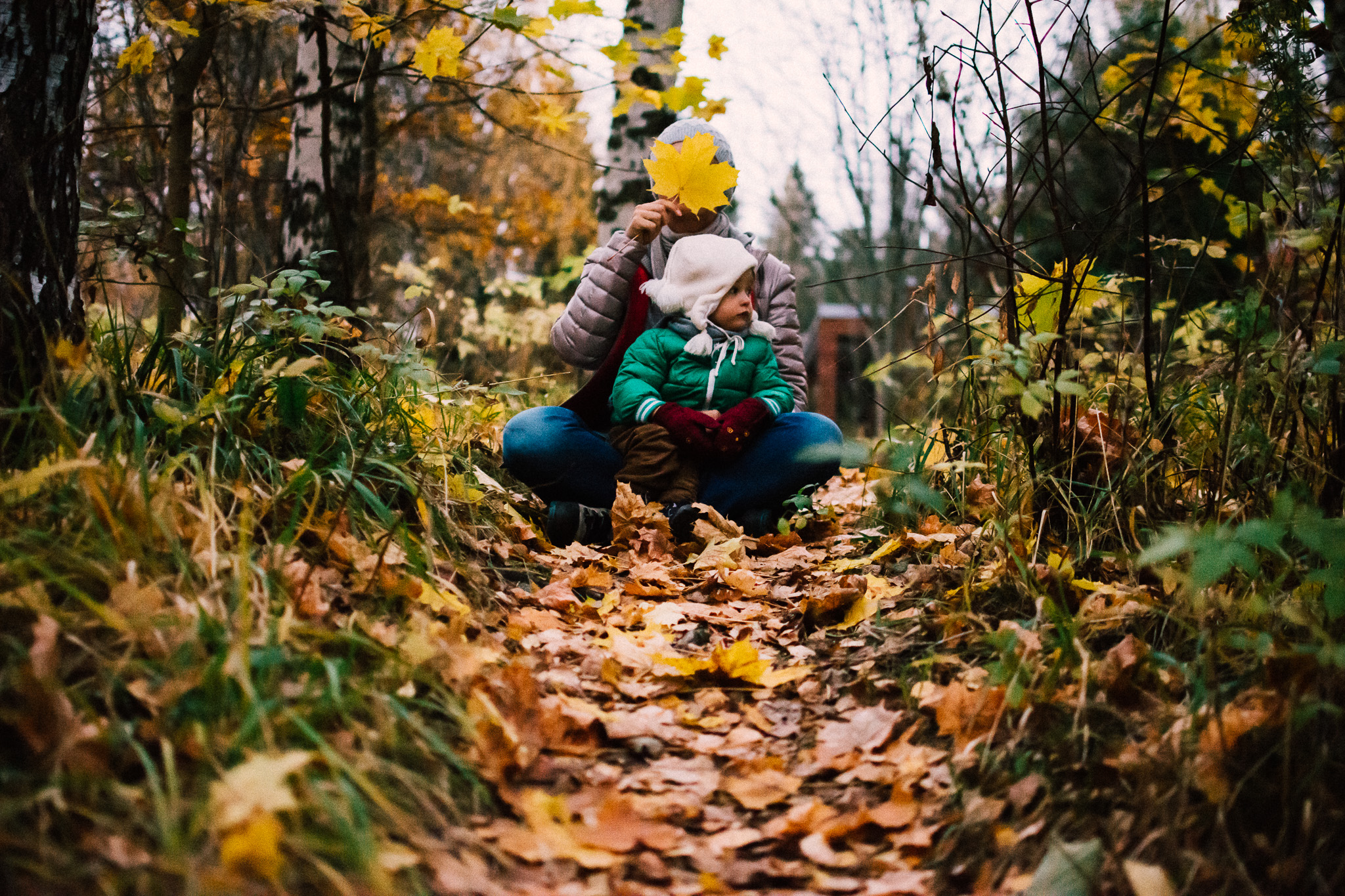 Child with mother sitting in autumn leaves