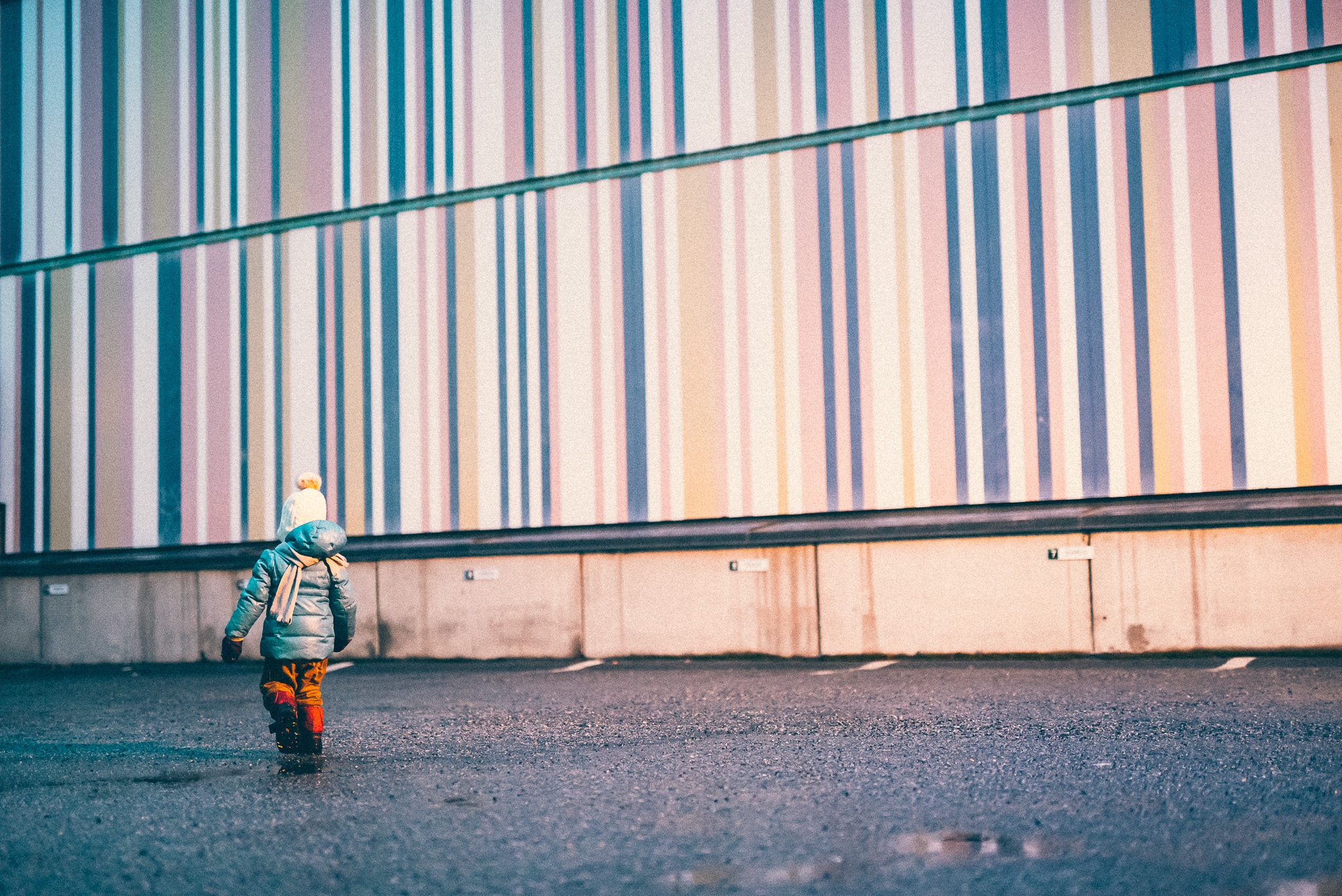 Child running in front of striped wall