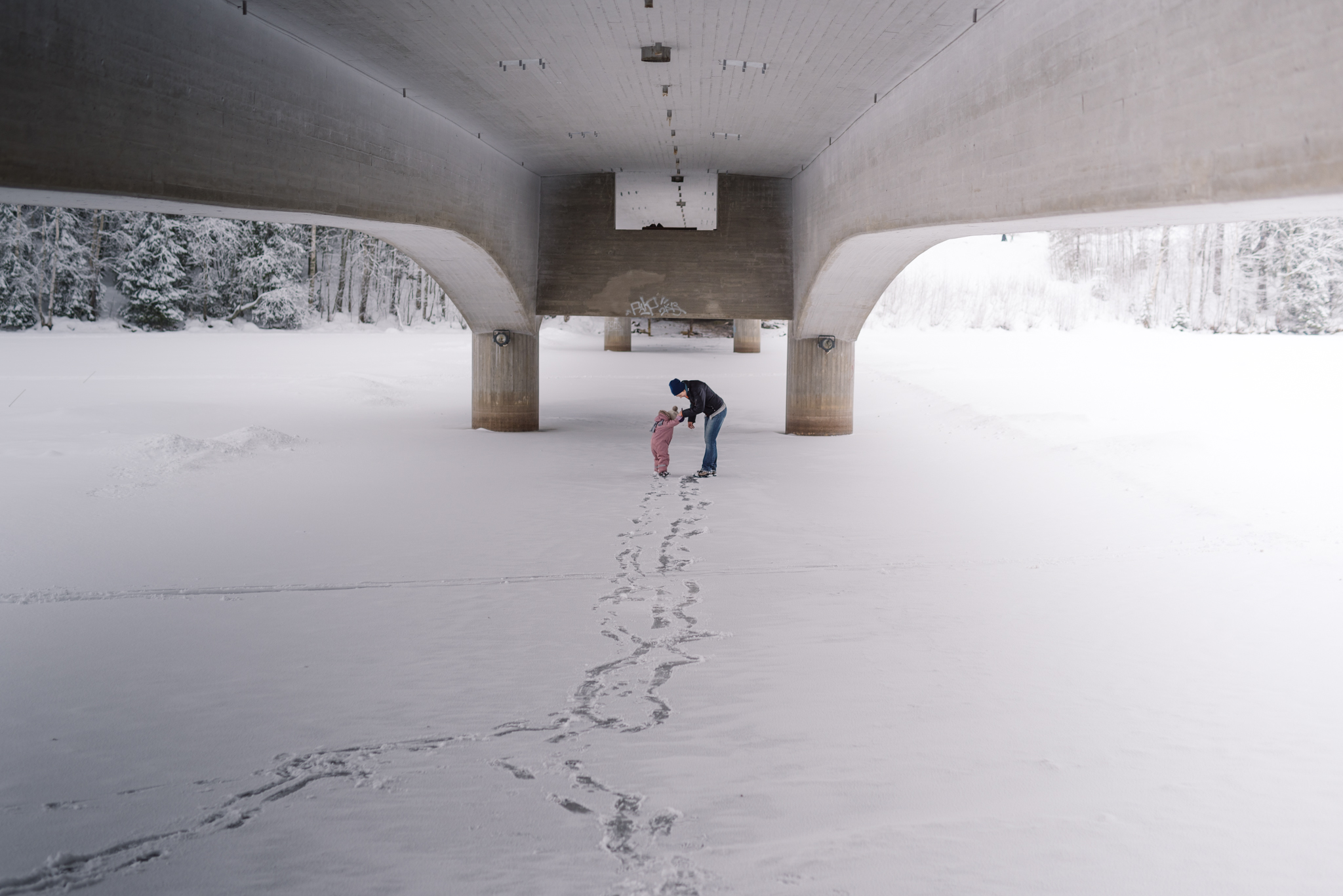 Mother and child standing under a bridge